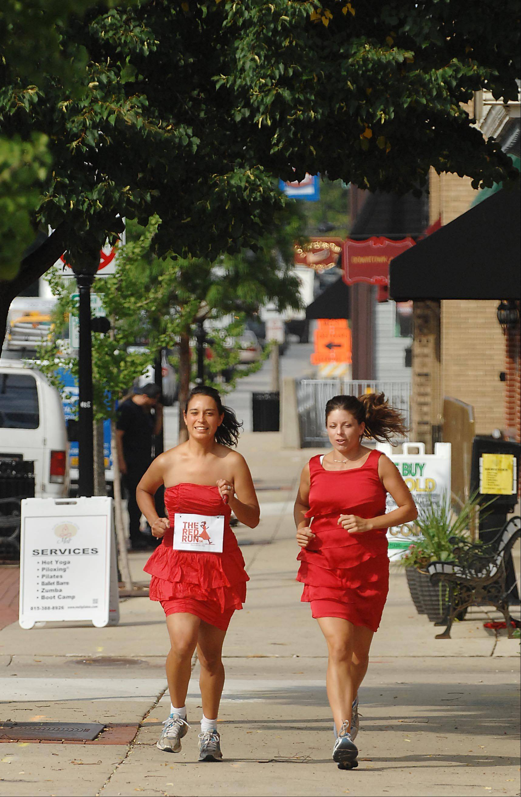 Cortina Nystad and Kristen Guerrieri, right, wear red dresses during their regular run at rush hour on Route 31 in Algonquin. The Algonquin moms wear red dresses after seeing photos of young Cambodian girls sold into the sex slave industry, who were also wearing red dresses. They have organized the Red Run 5K Run/Walk to benefit organizations who help combat the problem.