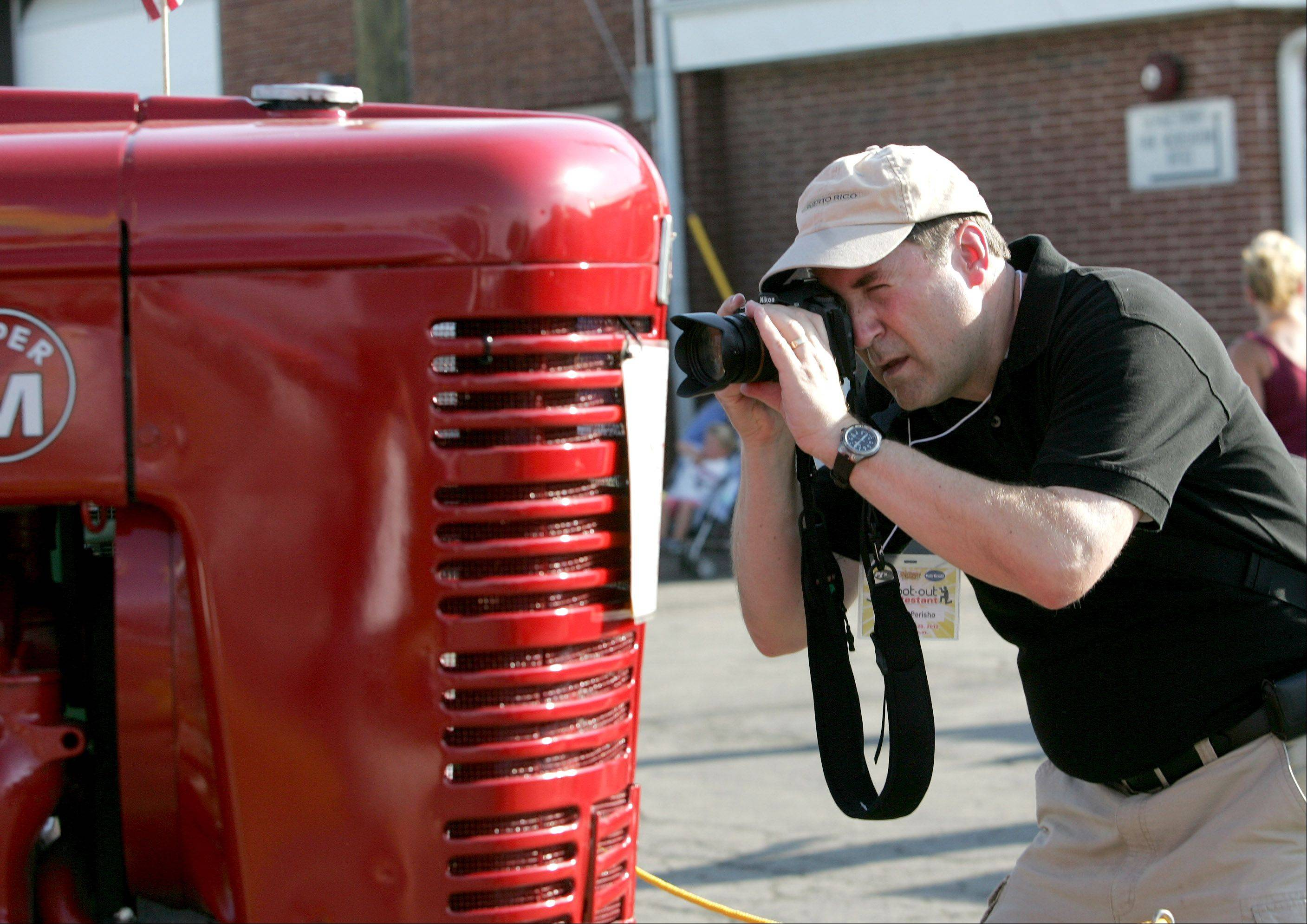 Gregory Perisho of Warrenville moves in to get a shot of a tractor during the photography Shoot Out competition during the opening day of the DuPage County Fair in Wheaton on Wednesday.