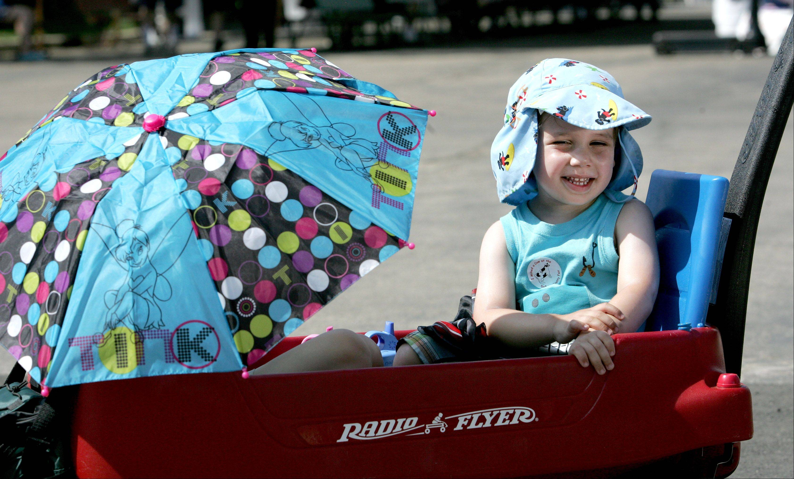 Matthew Jaeger, 3, of Glen Ellyn gets a ride in a wagon with his sister Angela, 4, shading herself under an umbrella, during the opening day of the DuPage County Fair in Wheaton on Wednesday.