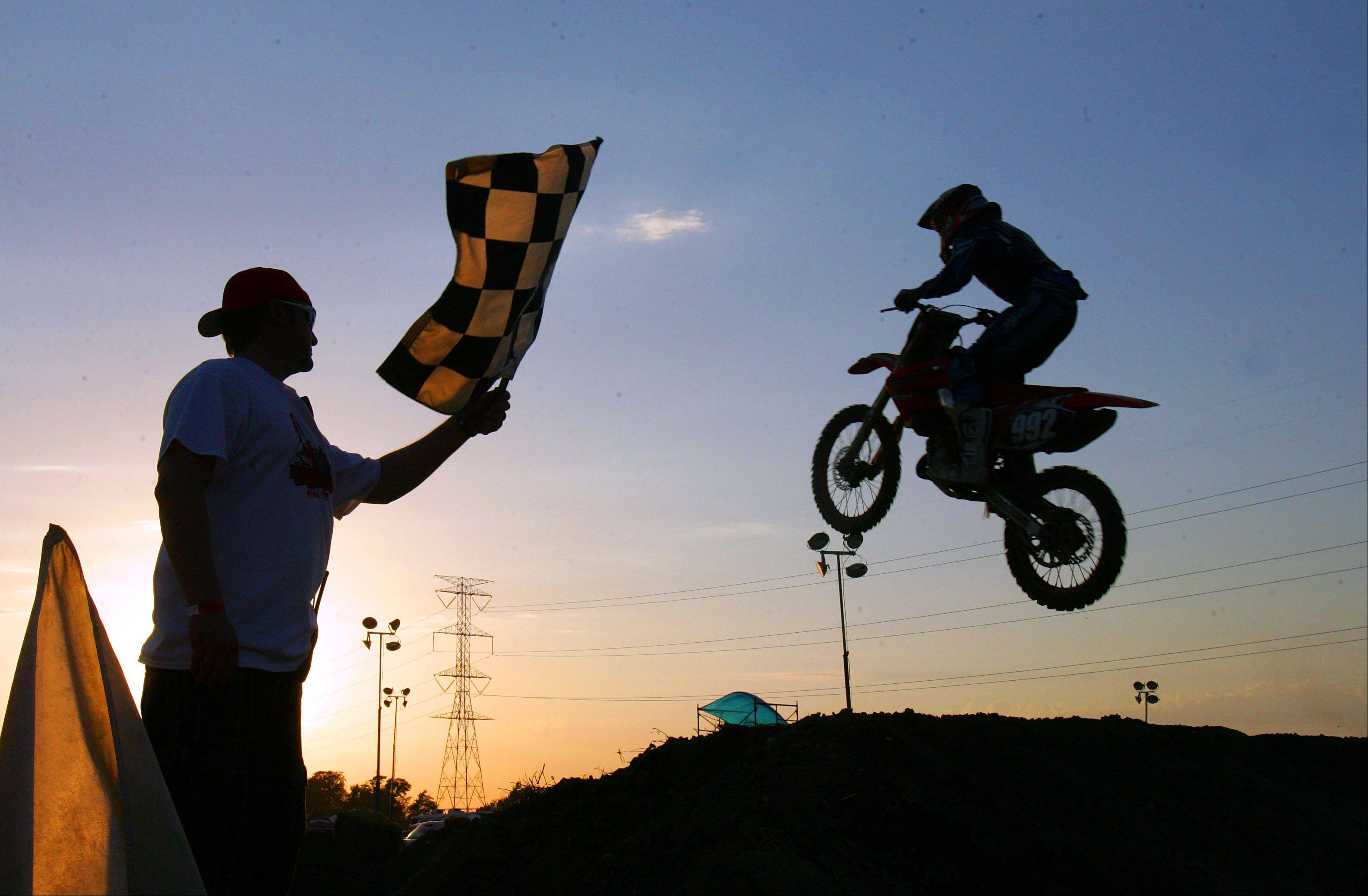 Motocross riders cross the finish line during the first night of the Lake County Fair Wednesday night in Grayslake.