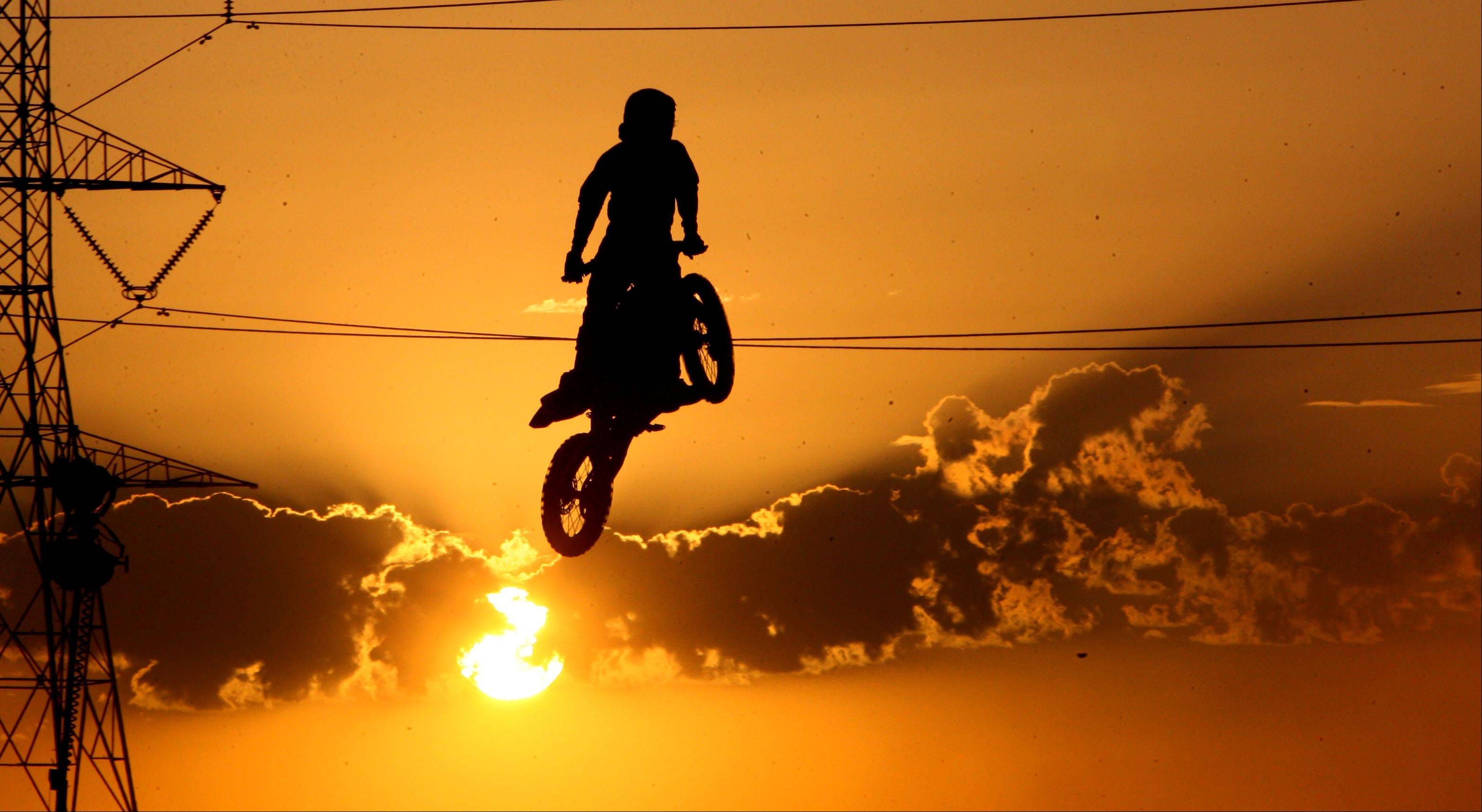 A motocross rider is silhouetted against the setting sun during the first day of the Lake County Fair Wednesday night in Grayslake.