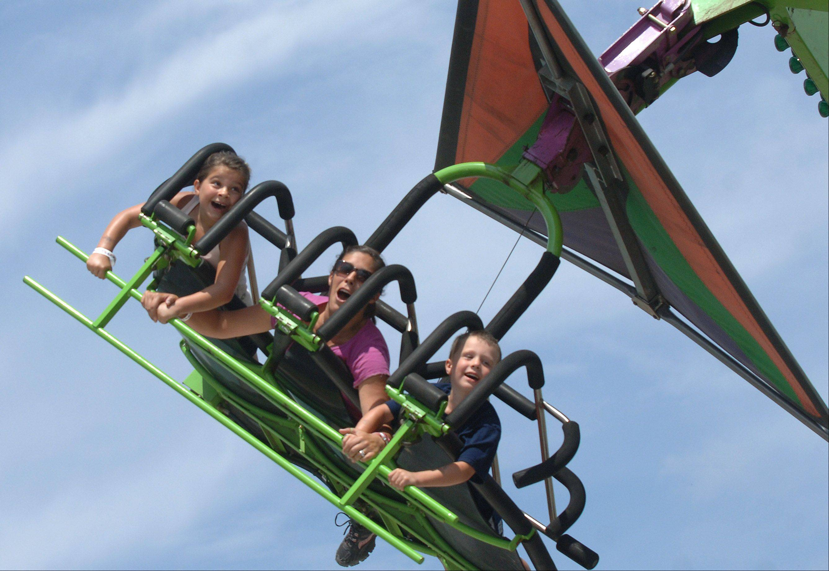 Crystal Lake family from left Grace Koeppen, 7, Laurie Koeppen and Andy Koepen, 5, ride the Cliff Hanger Thursday at the Lake County Fair in Grayslake.