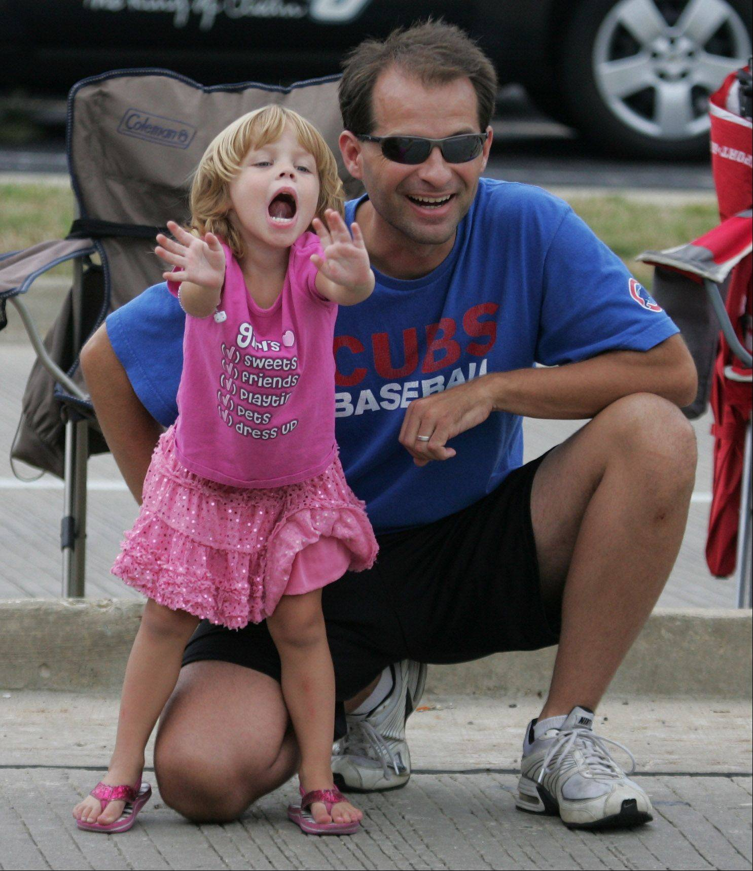 Natalie Miller, 3, of Barrington, screams for candy as she watches the parade with her father, Todd, during the Lake Zurich Alpine Fest parade Sunday along Route 22.