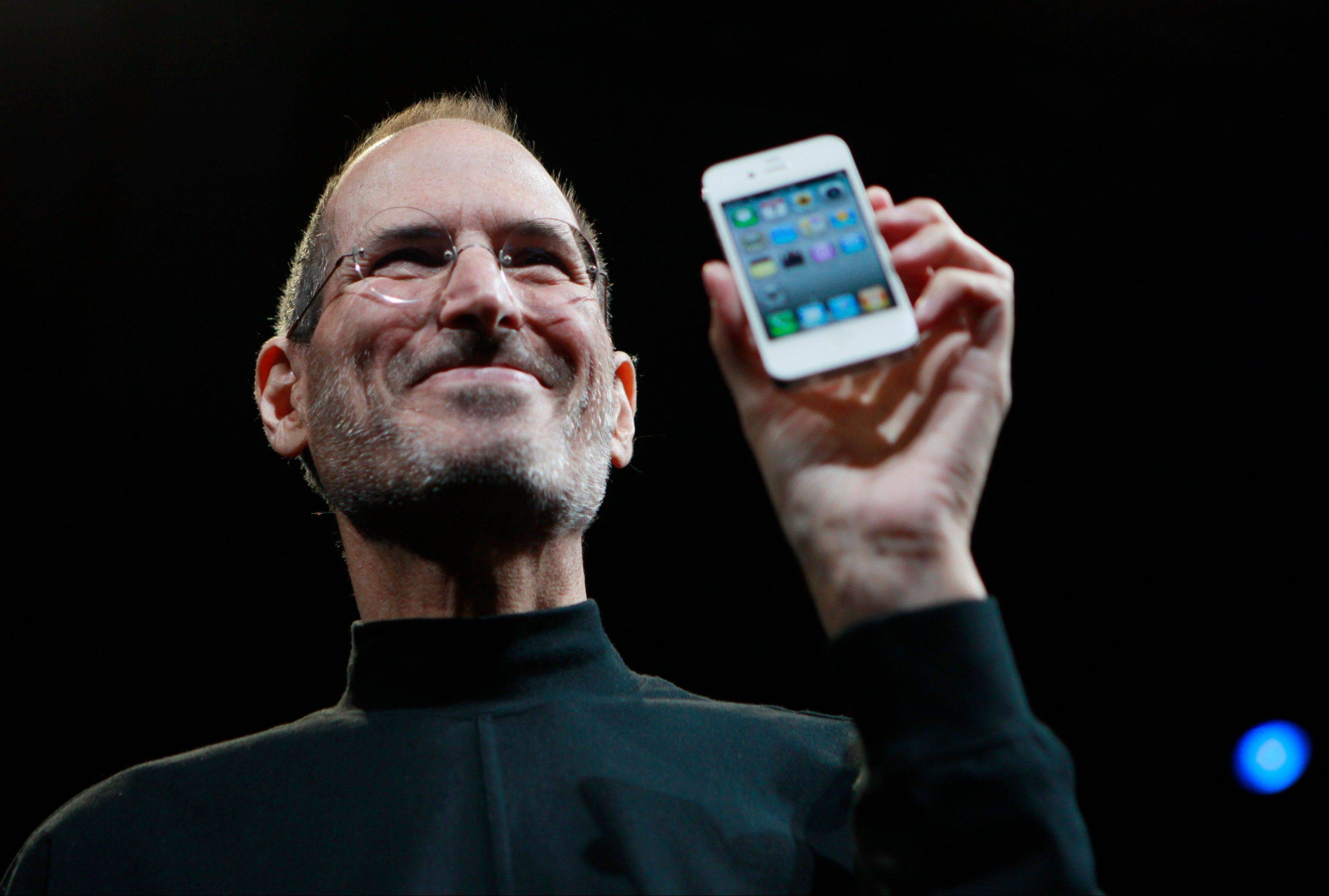 Apple CEO Steve Jobs, seen 2010, holds an iPhone at the Apple Worldwide Developers Conference in San Francisco. Two tech titans are squaring off in federal court this weeky in a closely watched trial over control of the worldwide smart phone and computer tablet markets.