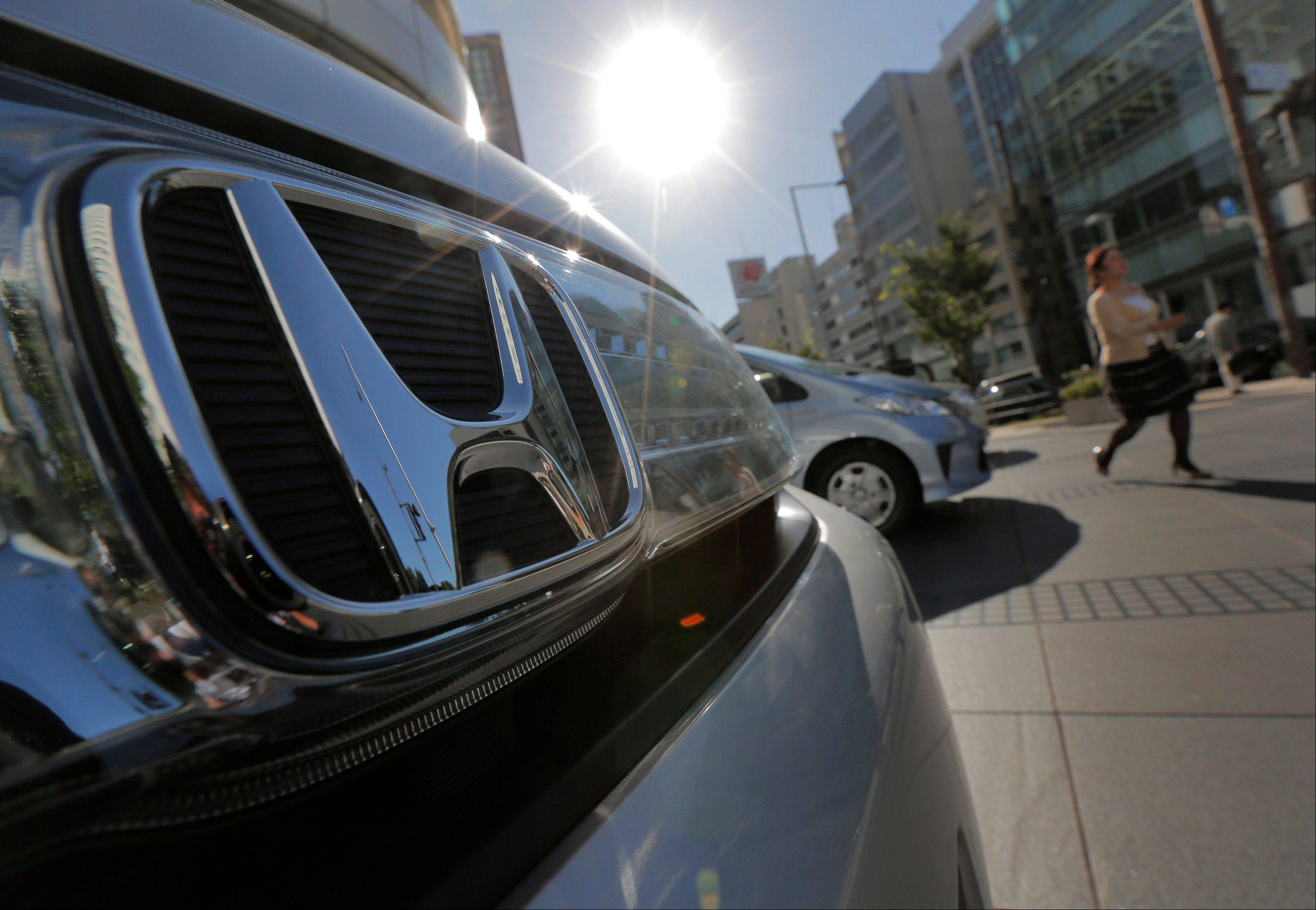 A woman walks by Honda Motor Co.�s vehicles on display in front of the Japanese automaker�s headquarters in Tokyo Tuesday.