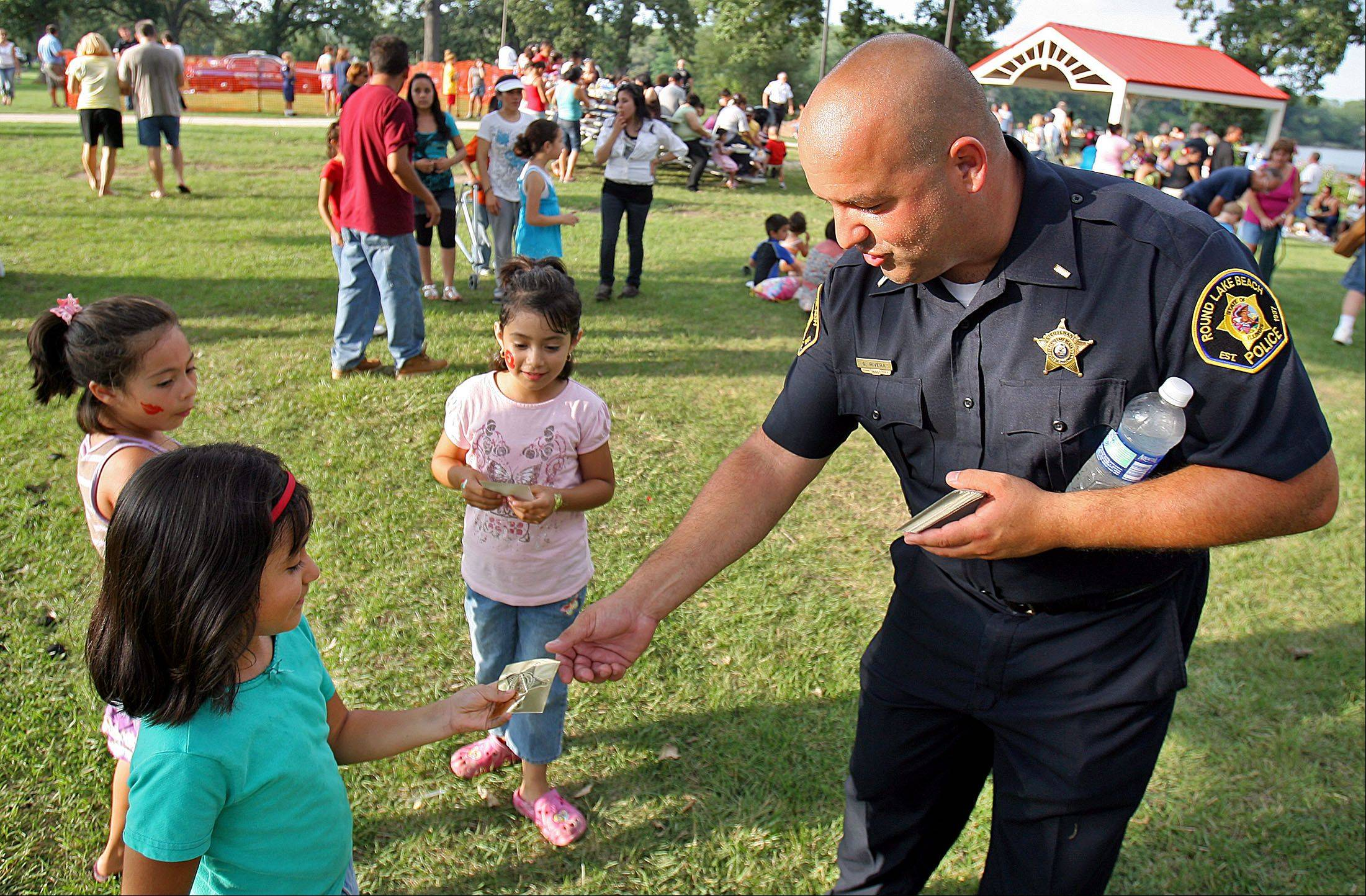 Round Lake Beach Police officer Gilbert Rivera hands out stickers to kids at an earlier Round Lake Beach Police National Night Out celebration. This year�s event will take place Aug. 7.