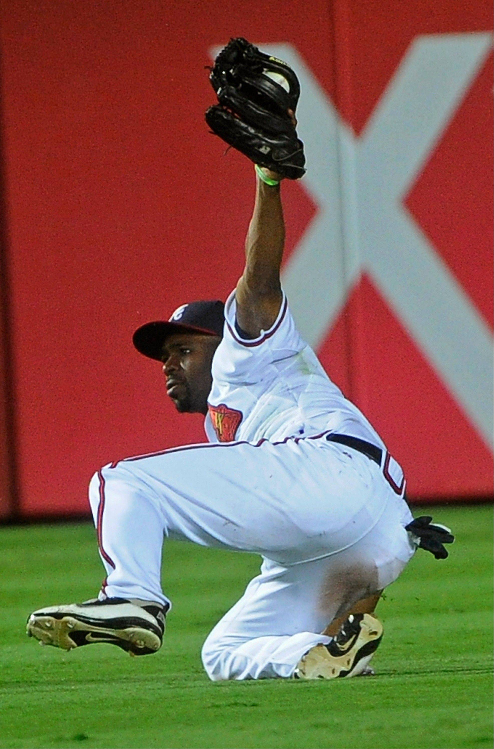 Braves center fielder Michael Bourn comes up with a diving catch on the fly ball hit by the Marlins� Bryan Petersen during the seventh inning Tuesday in Atlanta.