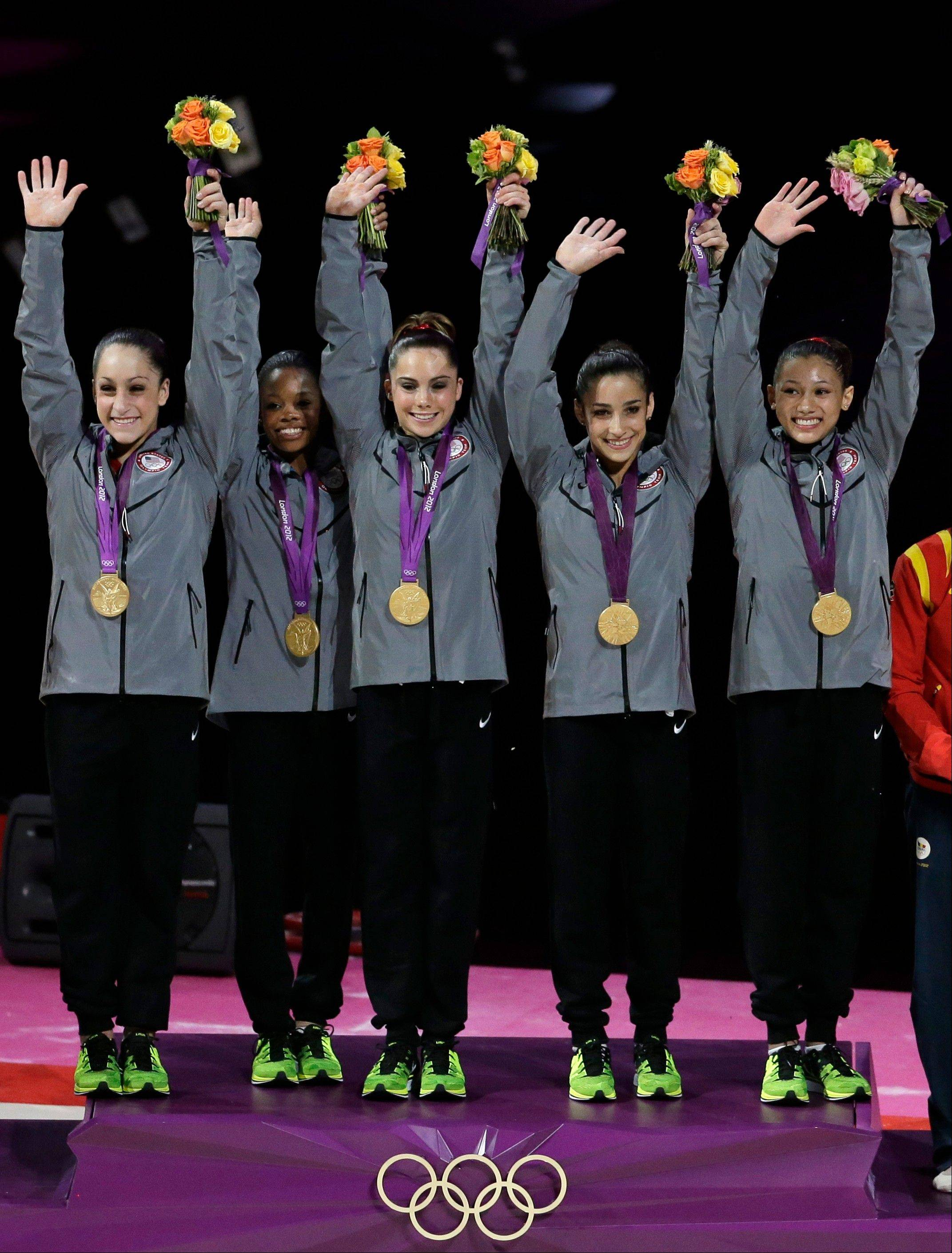 U.S. gymnasts, left to right, Jordyn Wieber, Gabrielle Douglas, McKayla Maroney, Alexandra Raisman, Kyla Ross raise their hands on the podium Tuesday during the medal ceremony at the 2012 Summer Olympics in London. They won the gold.
