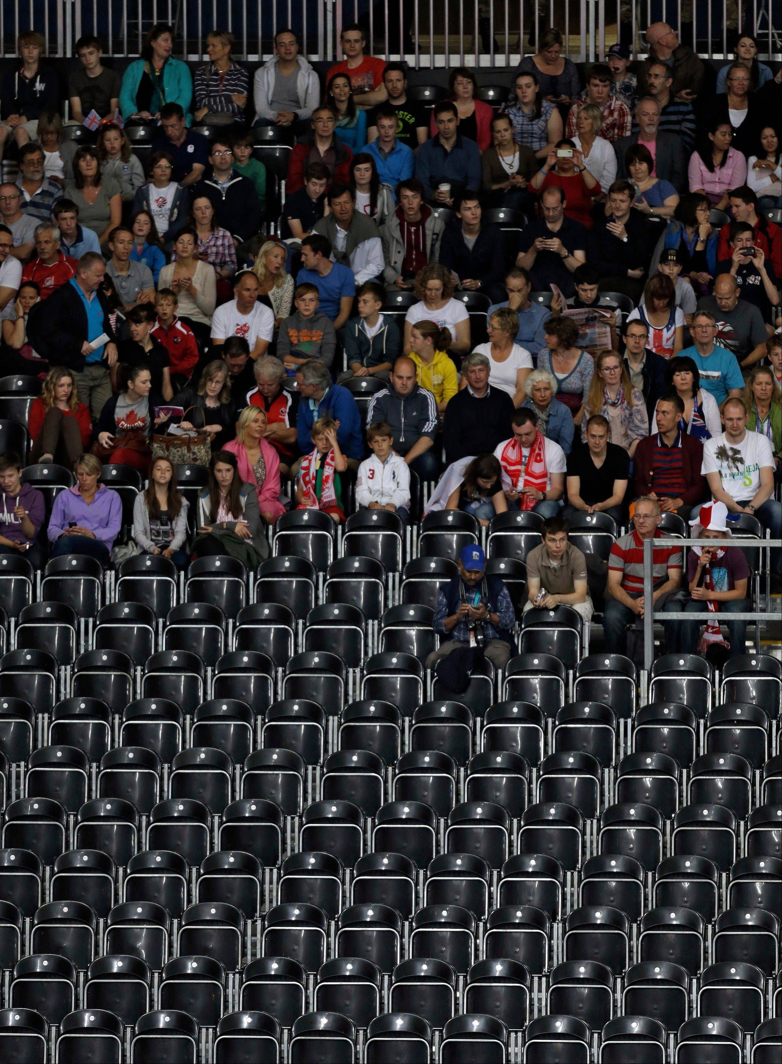 Spectators sits behind rows of empty seats during a men�s volleyball preliminary match between Tunisia and Serbia at the 2012 Summer Olympics Tuesday, July 31, 2012, in London.