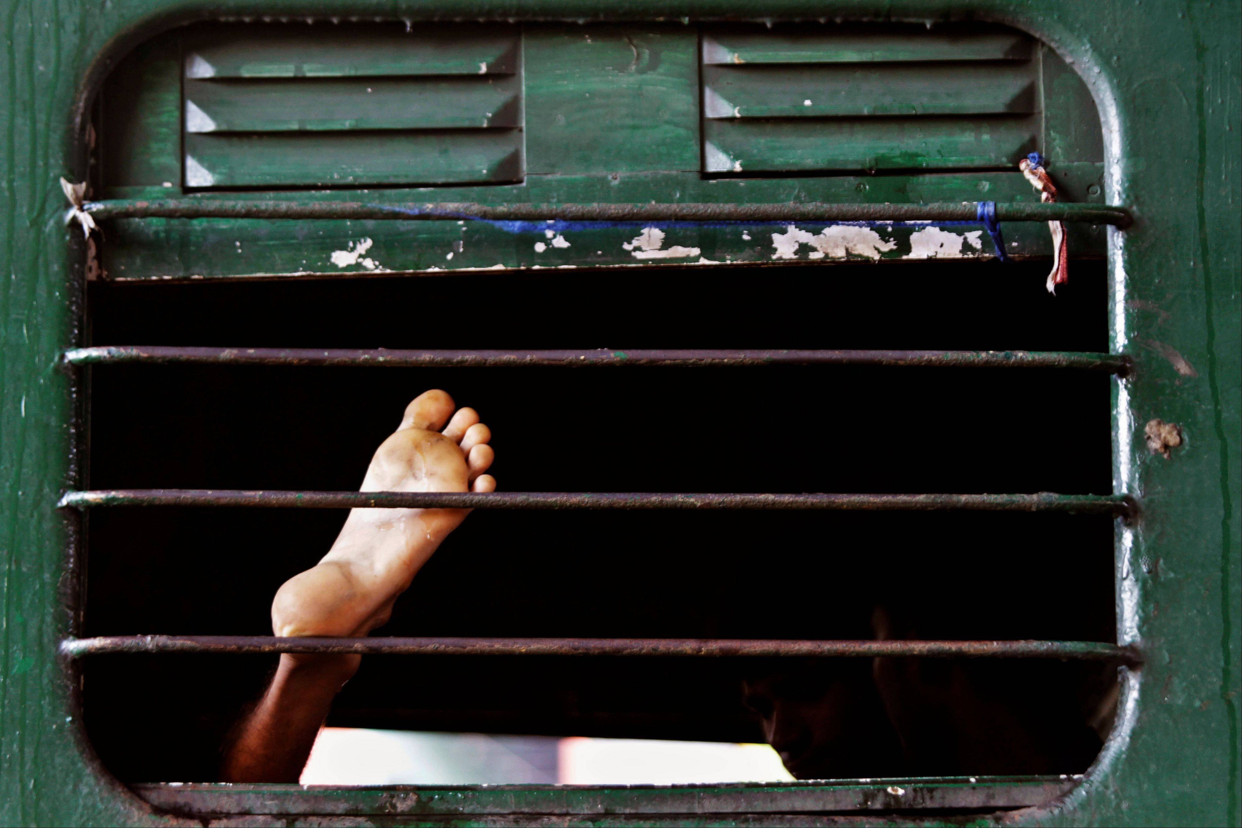 A stranded Indian train passenger rests inside a railway coach as he waits for the train service to resume following a power outage in Kolkata, India, Tuesday, July 31, 2012. India's energy crisis cascaded over half the country Tuesday when three of its regional grids collapsed, leaving 620 million people without government-supplied electricity for several hours in, by far, the world's biggest-ever blackout.