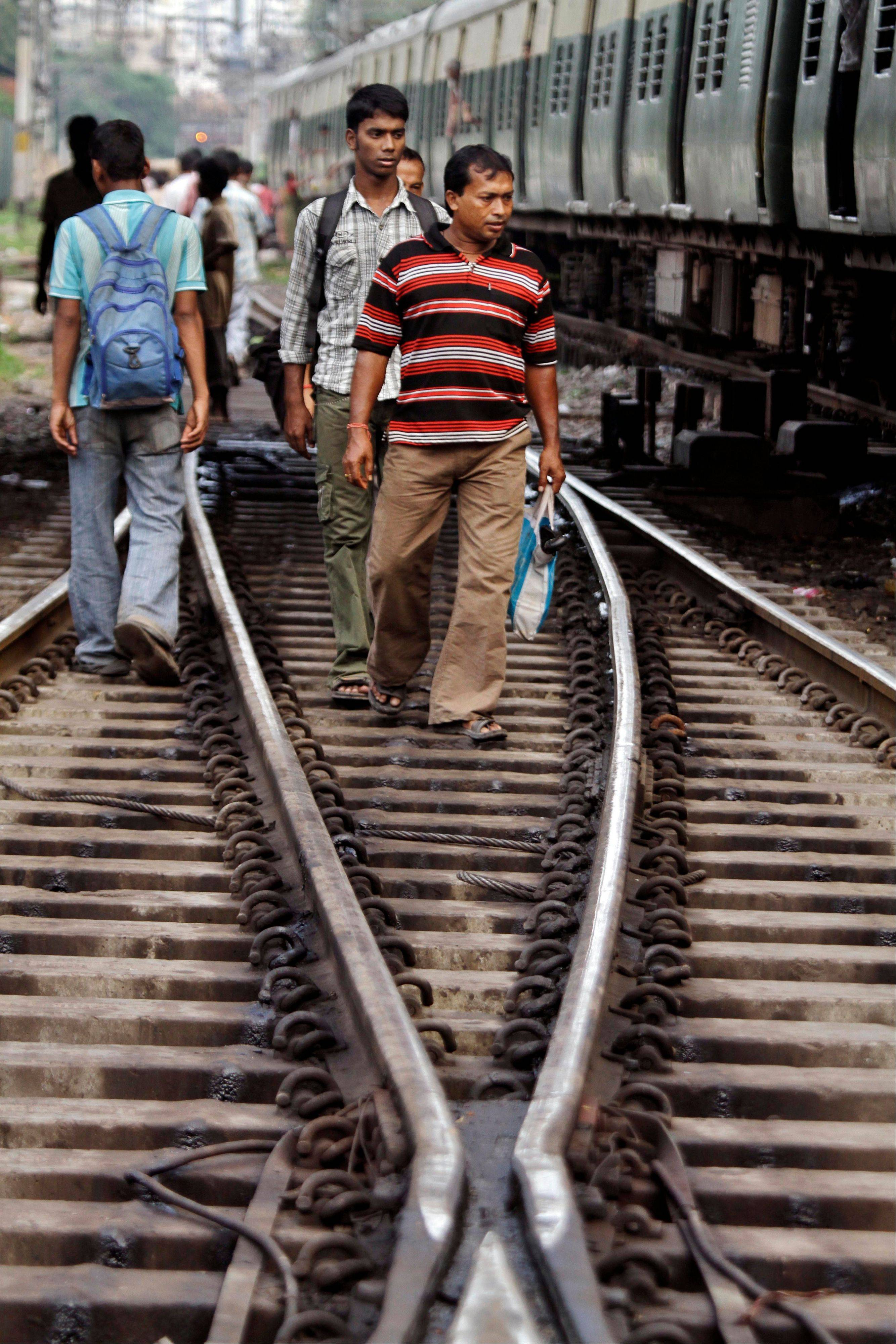 Indian passengers walk along railway track near a stalled local train at the Sealdah station following power outage in Kolkata, India, Tuesday, July 31, 2012. India's energy crisis cascaded over half the country Tuesday when three of its regional grids collapsed, leaving 620 million people without government-supplied electricity for several hours in, by far, the world's biggest-ever blackout. Hundreds of trains stalled across the country and traffic lights went out, causing widespread traffic jams in New Delhi.