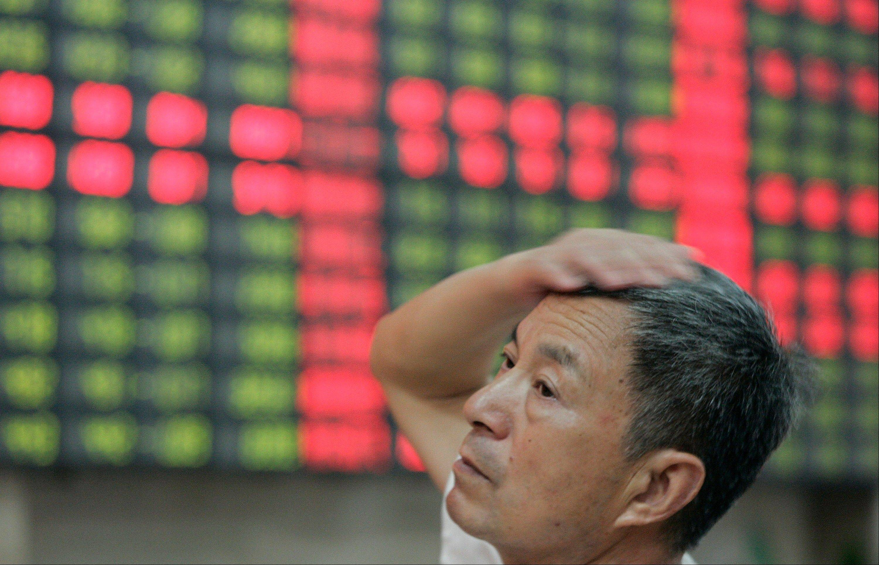 An investor looks at a stock price monitor at a private securities company in Shanghai, China, Tuesday.