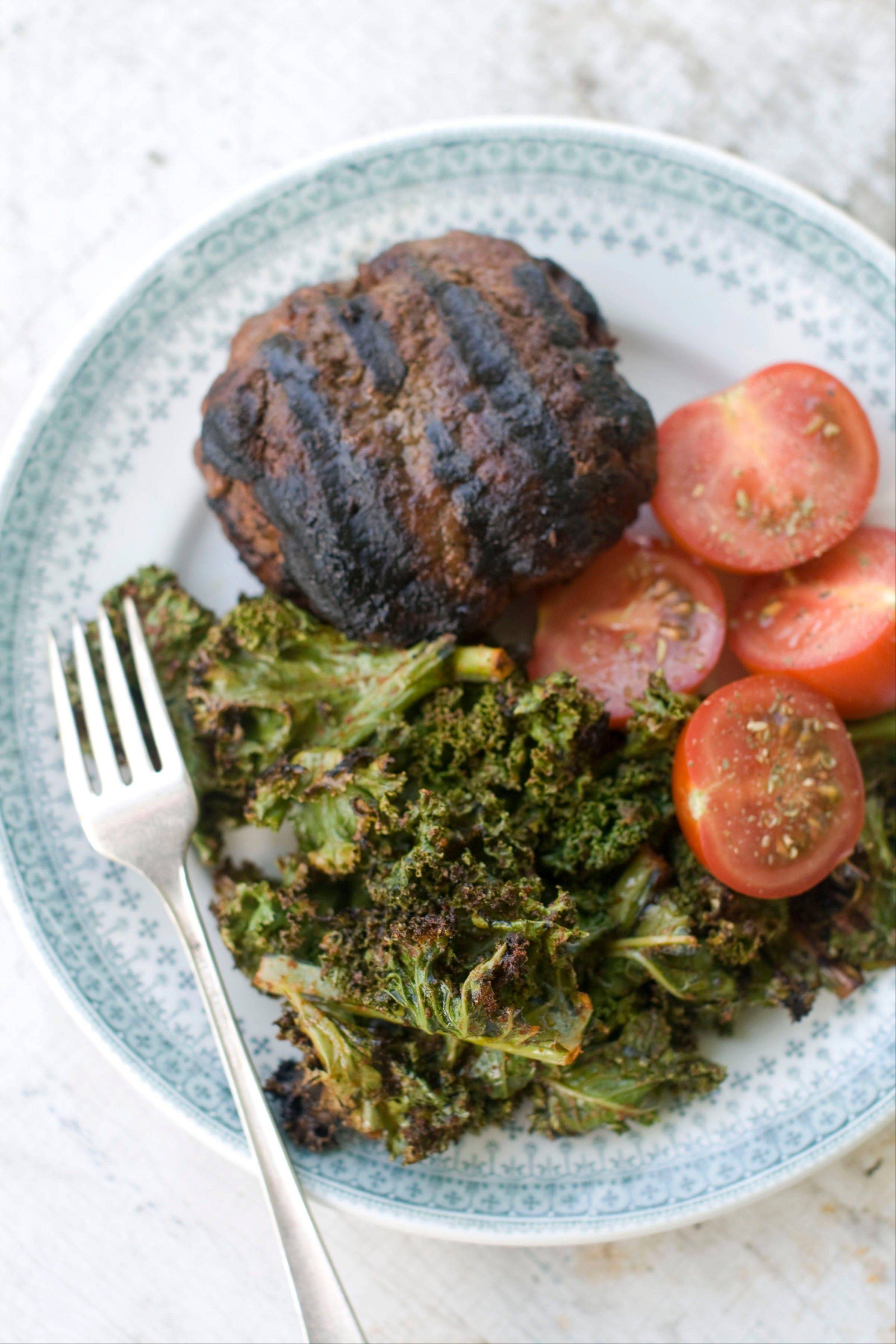 Garlicky grilled kale served with a burger and fresh tomatoes makes a perfect summer meal.