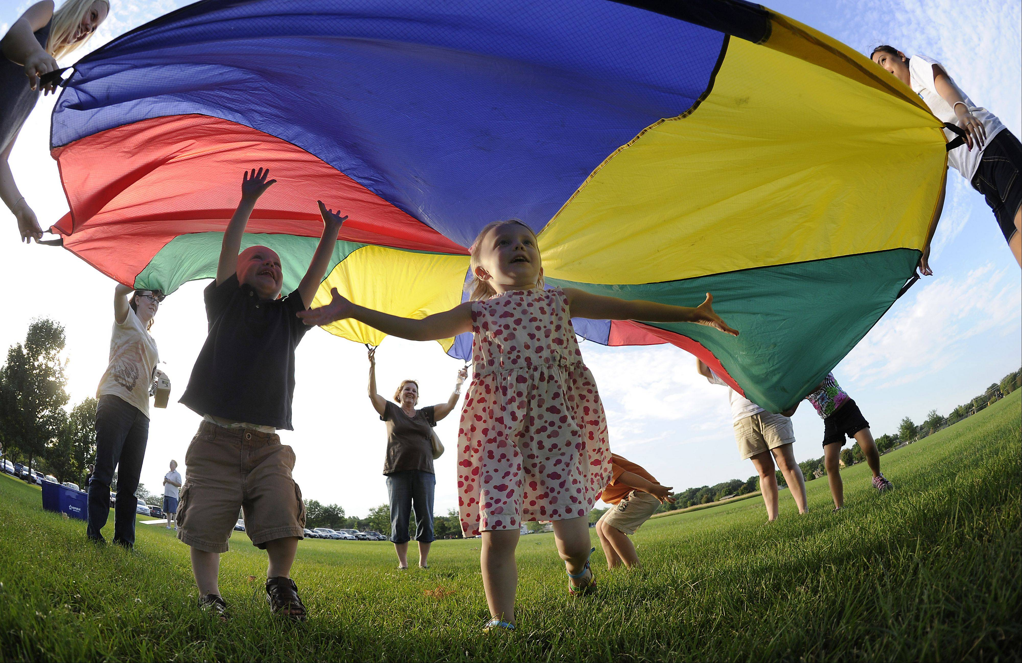 DAILY HERALD FILE PHOTOWhitney Dumke, 4, of Plainfield plays under a colorful parachute as part of Bartlett's celebration of National Night Out last year.