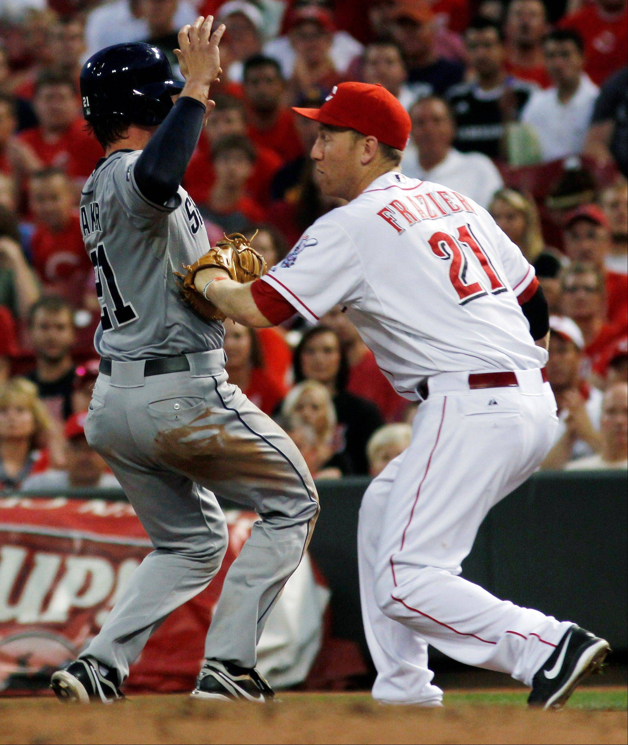 The Reds' Todd Frazier tags San Diego's John Baker out on a rundown to complete a double play in the fifth inning Tuesday in Cincinnati.