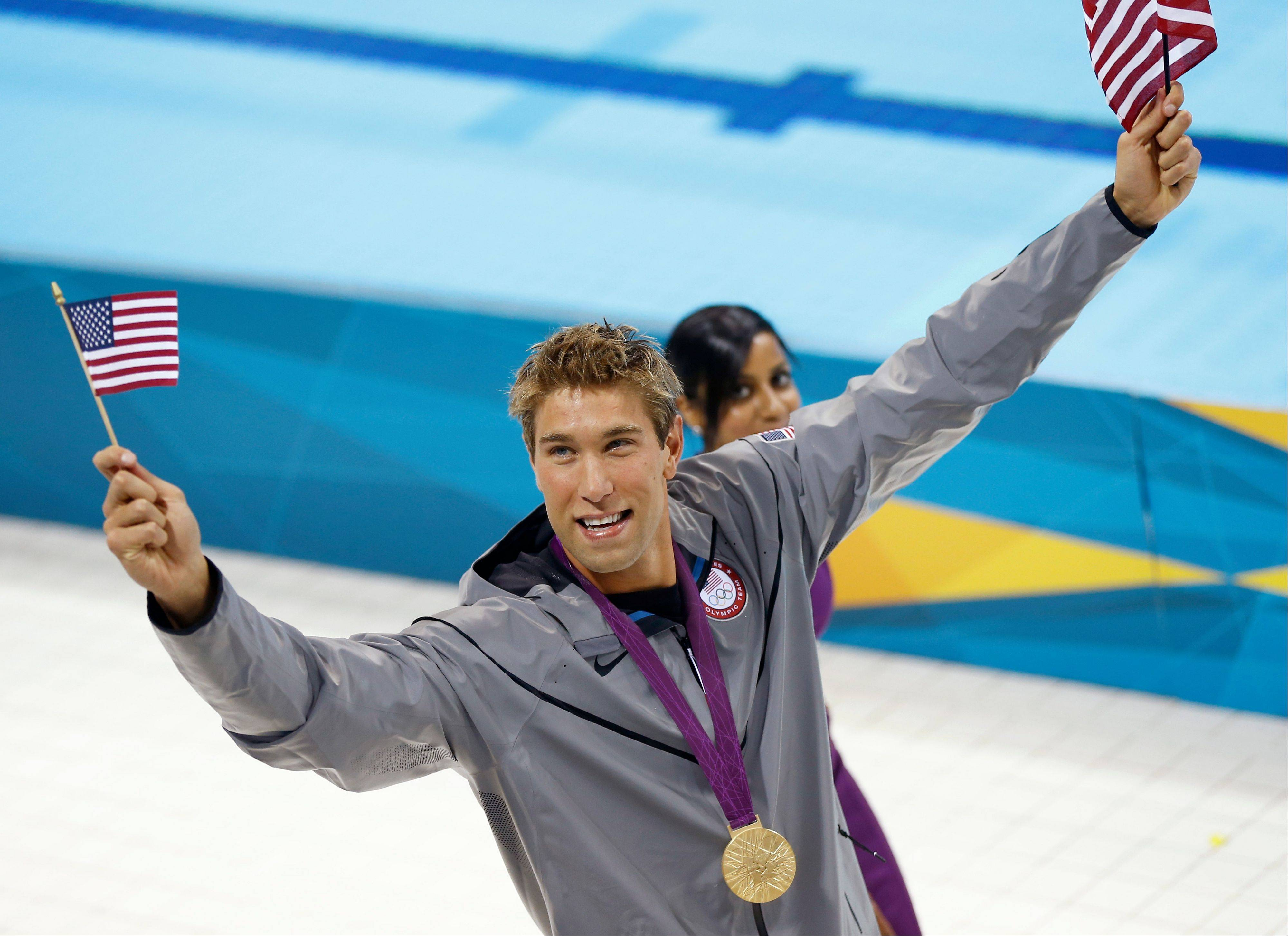 United States' gold medalist Matthew Grevers waves American flags as he walks at the Aquatics Centre in London after a medal ceremony for the men's 100-meter backstroke swimming final.