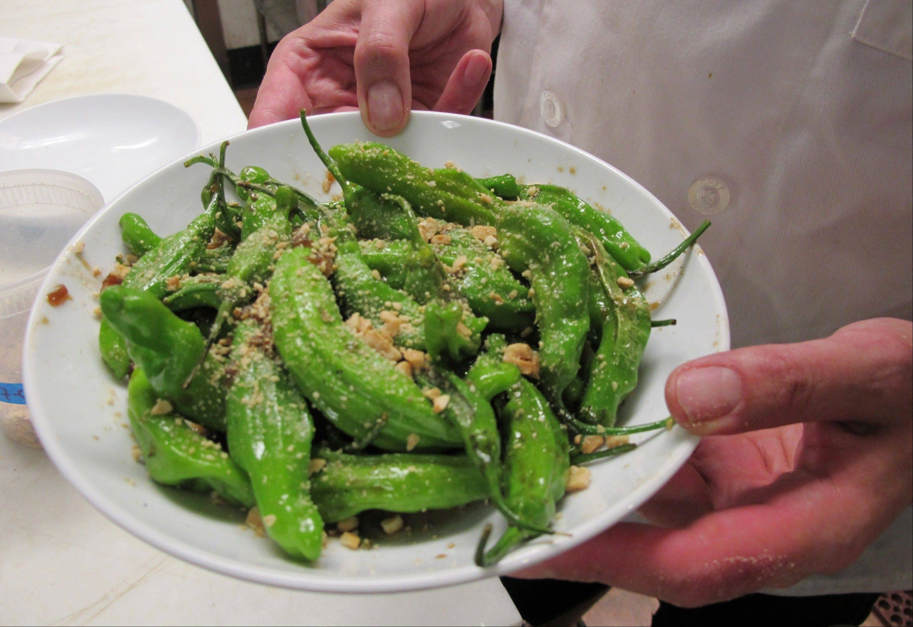 Chef Dan Jacobs holds a plate of shishito peppers at Roots Restaurant and Cellar in Milwaukee. Jacobs has noticed this summer's extreme heat has helped make some peppers extra-spicy.