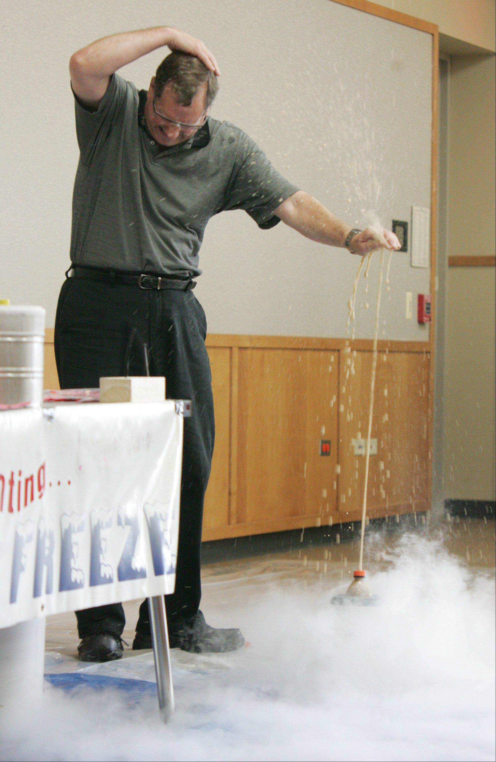 Jerry Zimmerman, also known as Mr. Freeze of Fermilab, covers up as a soda pop explodes after being placed in liquid nitrogen. Zimmerman demonstrated the fun properties of cryogenics for children at Ela Area Public Library.