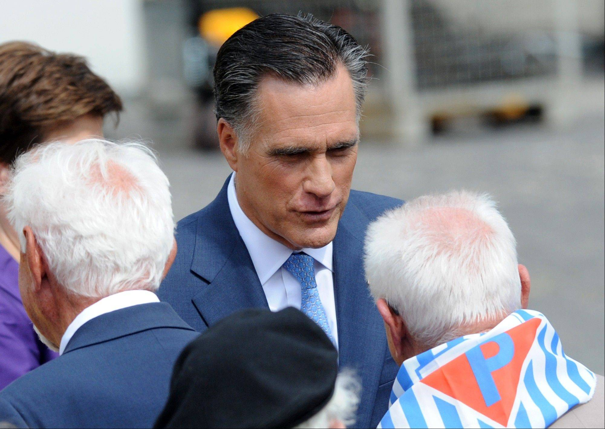 U.S. Republican presidential candidate, former Massachusetts Gov. Mitt Romney, facing camera, speaks with Polish World War II veterans and a survivor of a Nazi concentration camp after laying a wreath at the Warsaw 1944 Uprising monument in Warsaw, Poland, Tuesday, July 31, 20