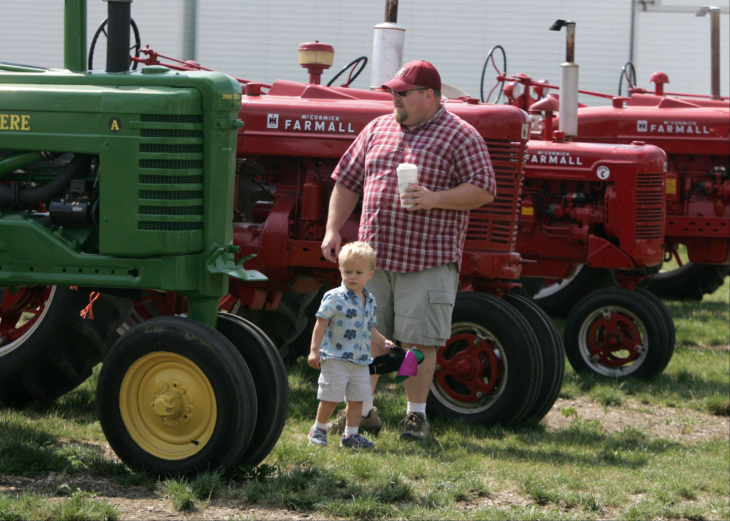 David Martin of McHenry and his son, Isaac, 2, look at tractors at the Lake County Farm Heritage Association Inc. exhibit during last day of the 84th Annual Lake County Fair Sunday in Grayslake. Fair organizers say attendance was up this year for the first time since moving to a new fairgrounds in 2009.