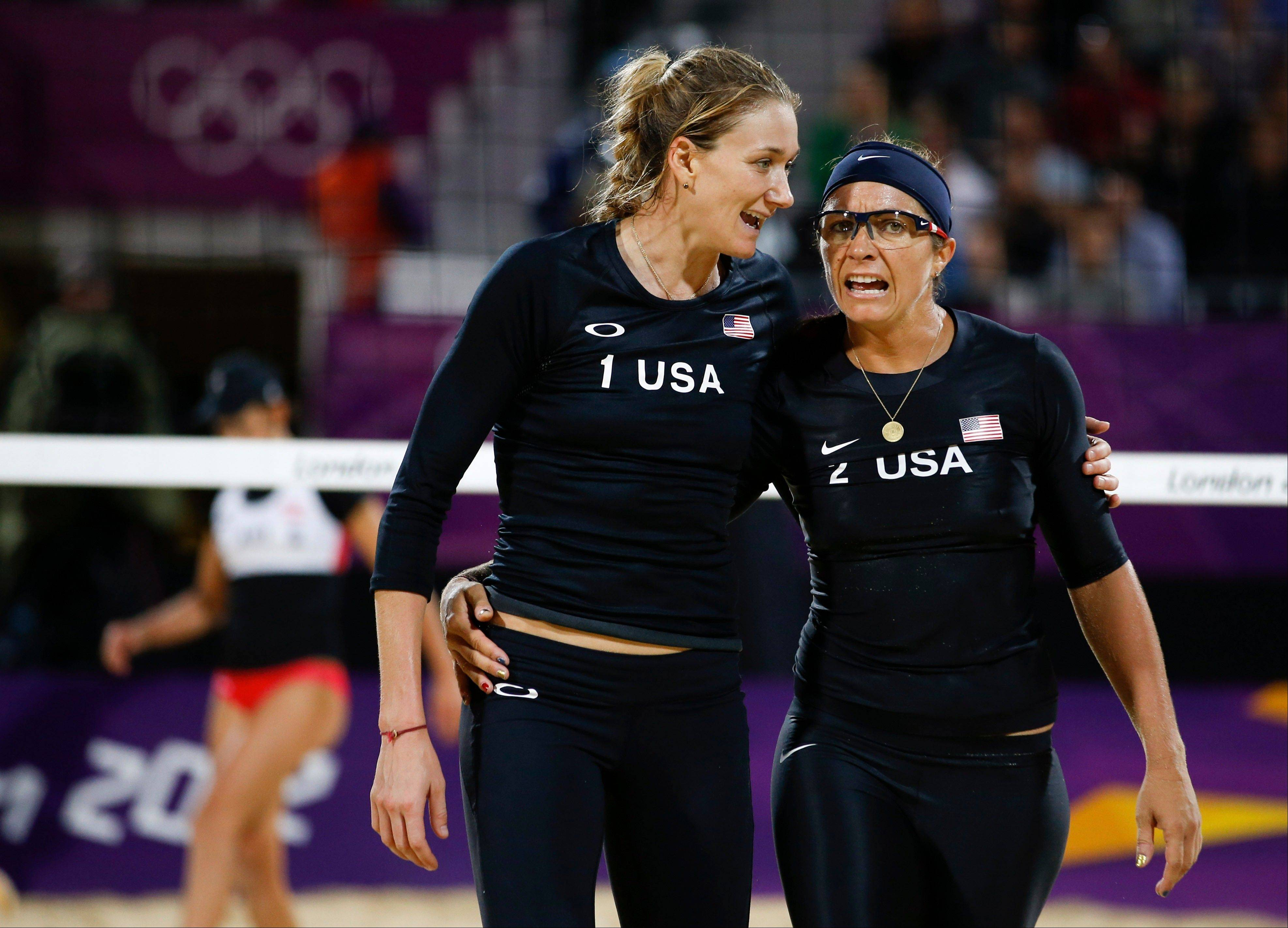 United States' Kerri Walsh, left, and Misty May-Treanor chat during a beach volleyball match against Austria's Doris Schwaiger and Stefanie Schwaiger at the 2012 London Olympics on Thursday. The defending champion Americans won their match, but waiting until NBC's prime-time show to find out was difficult, since the match was played hours earlier.