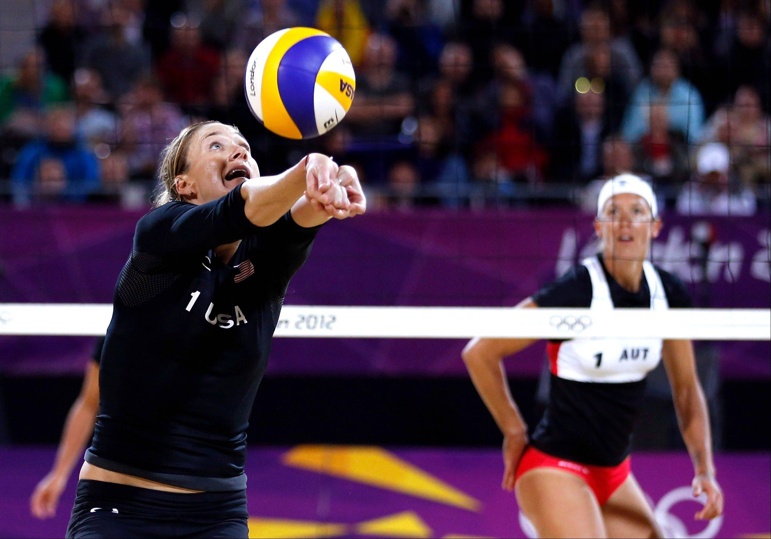 United States beach volleybal player Kerri Walsh, left, returns the ball as Austria's Stefanie Schwaiger looks on Wednesday during match at the 2012 Summer Olympics.