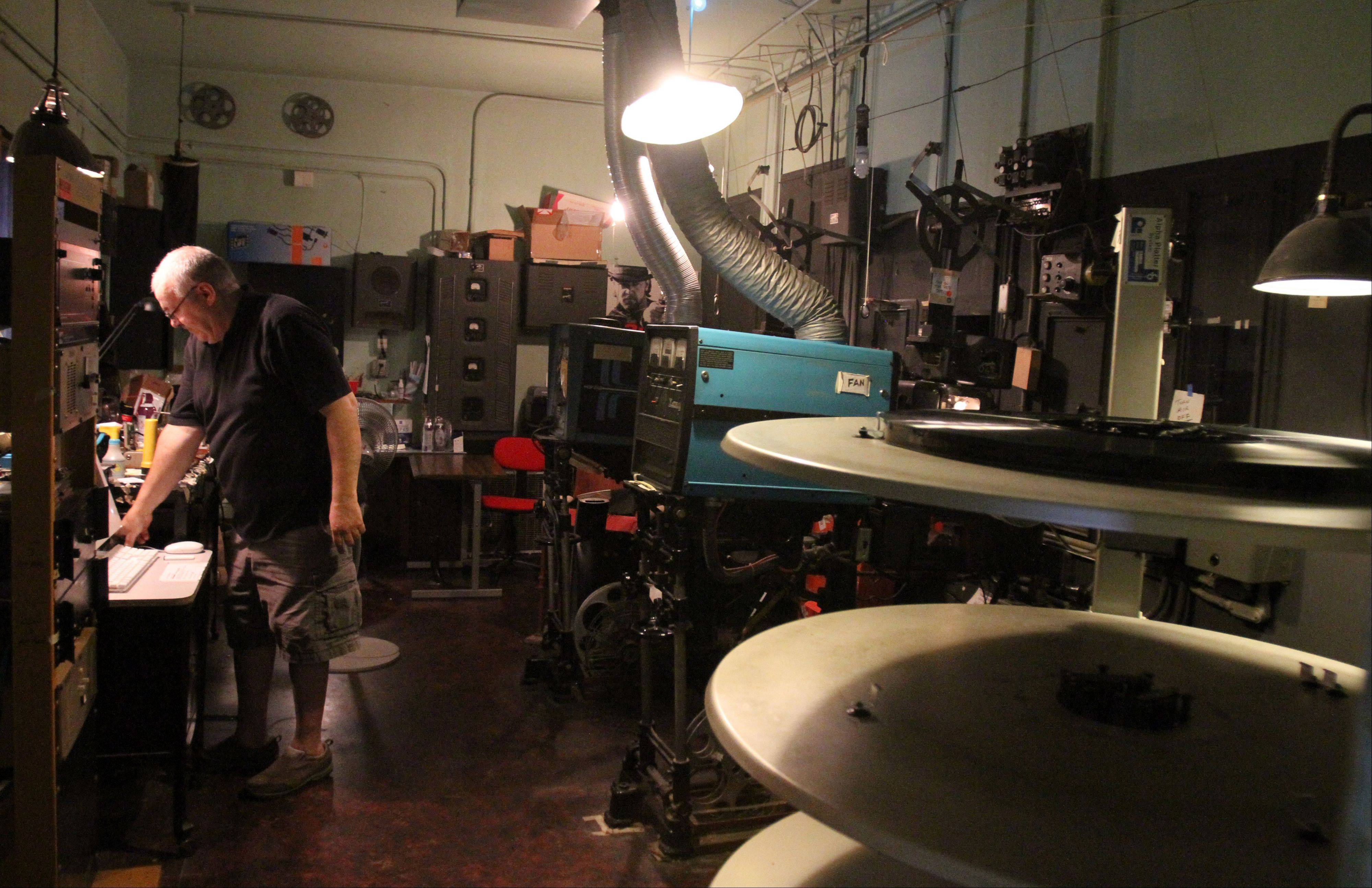 The Catlow theater co-owner Tim O'Connor in the film projection room with the 10940-50s Simplex XL film projector, at right, that is being used at the theater in Barrington.