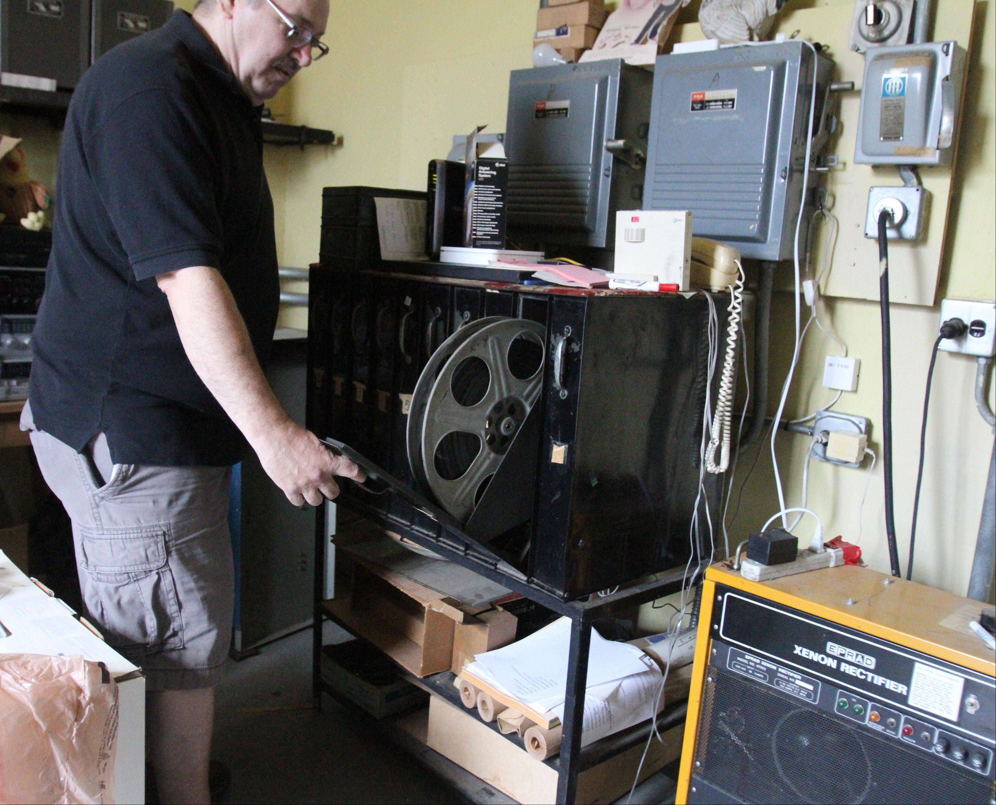 Catlow theater co-owner Tim O'Connor displays an older type film storage system that is no longer used.
