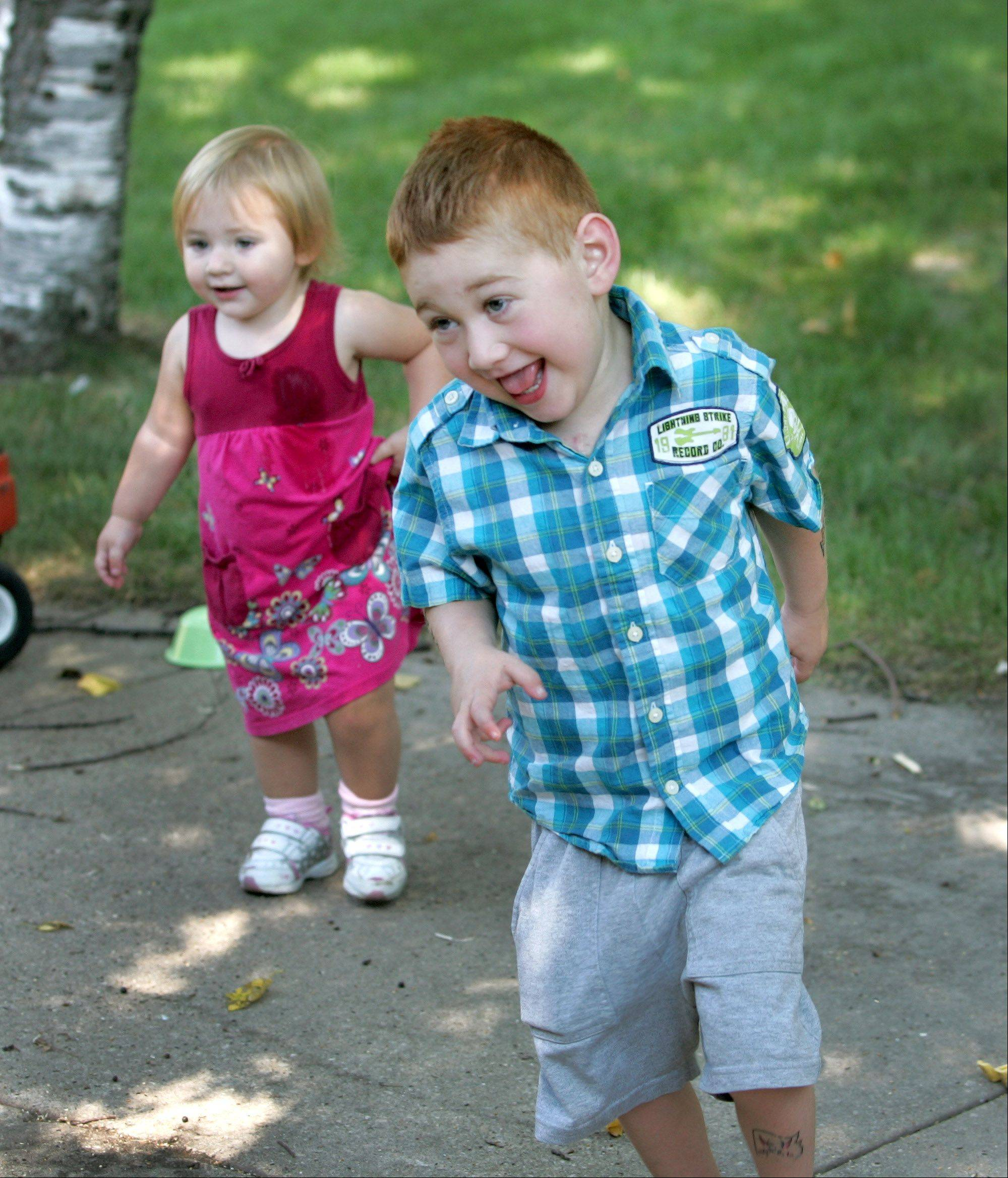 Tim Grobart, 5, of Lombard, plays outside Friday with his 18-month-old sister Rosie. Tim, who was diagnosed with a rare heart defect at 4 months old, underwent the first heart transplant at the new Lurie Children's Hospital in Chicago.