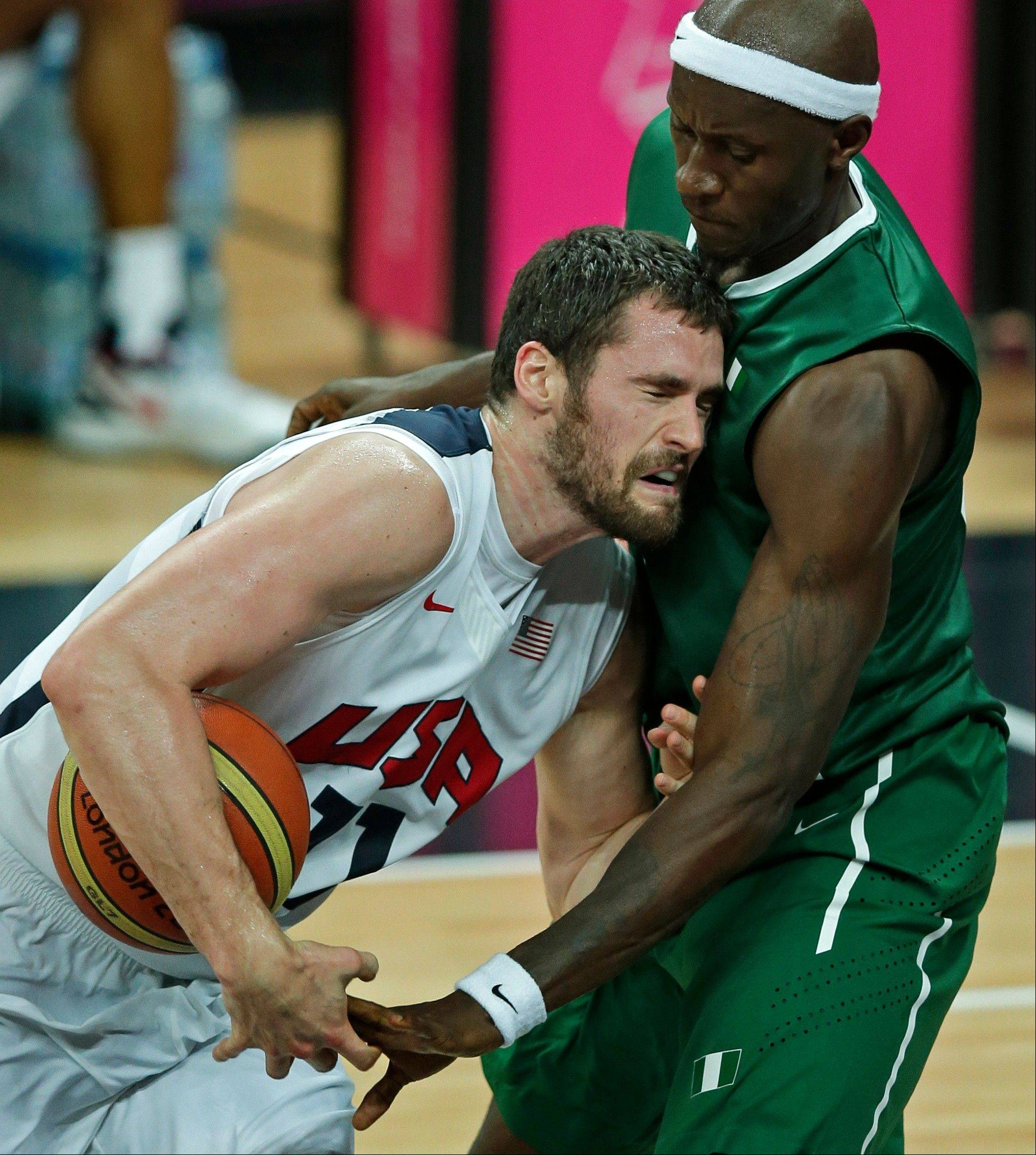 Nigeria's Richard Oruche, right, tries to steal the ball from United States' Kevin Love during a men's basketball game Thursday at the 2012 Summer Olympics.