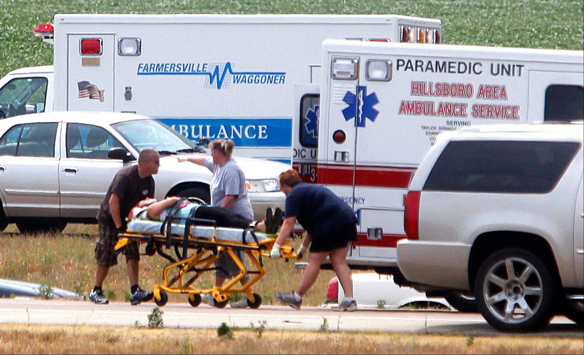 First responders wheel a crash victim to a waiting ambulance at the scene of a charter bus crash on Interstate 55 near Litchfield on Thursday.