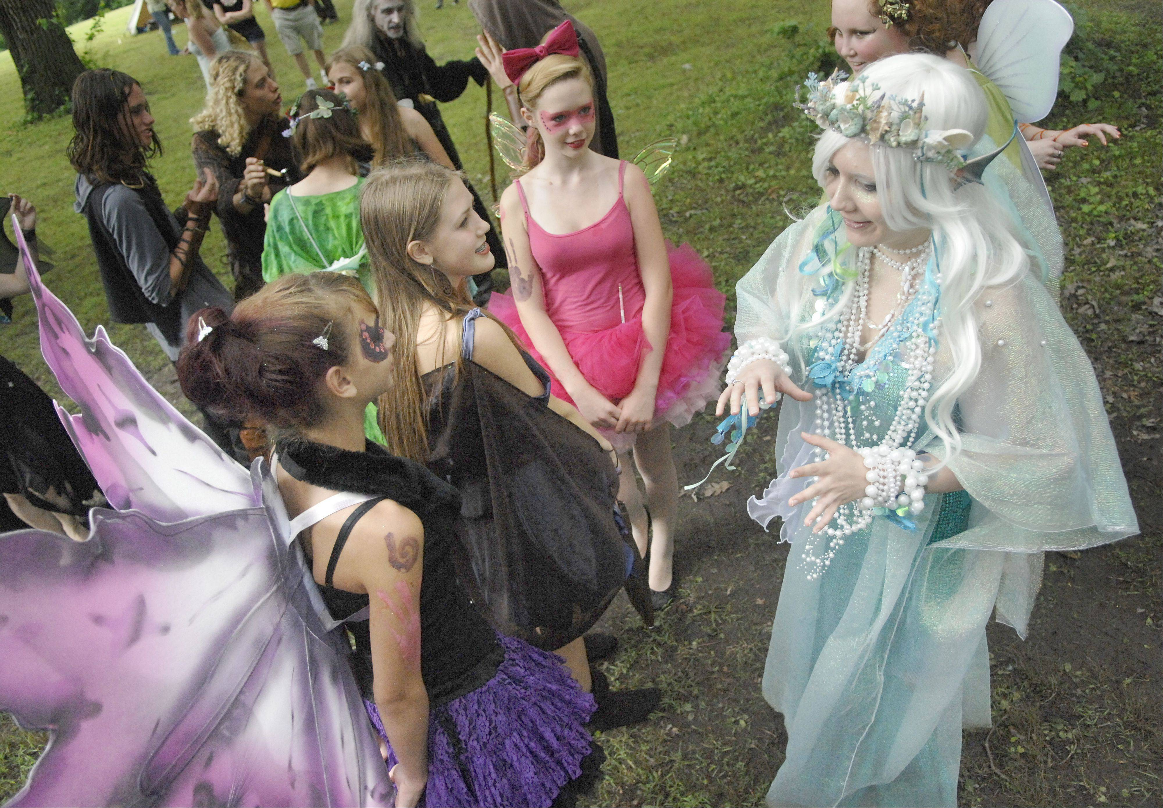 Marlo Musiel of Villa Park as Lemaris, right, speaks to fellow fairies from the Fairy Realm during last year's World of Faeries Festival at Vasa Park in South Elgin.