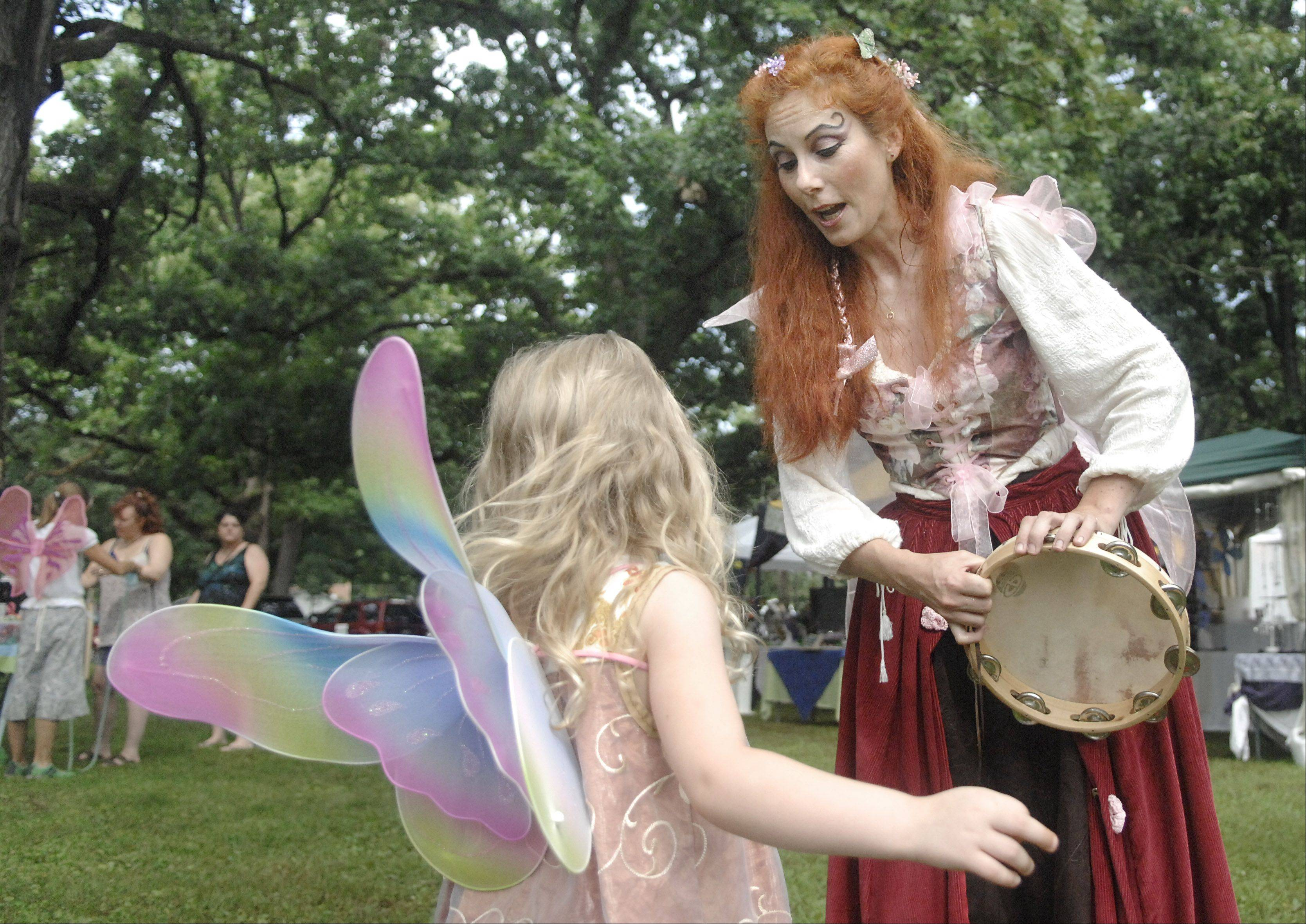 The Ruby Ruse Fairy, played by Amy Christensen of Chicago, sings to Elora Jaecks, 4, of Naperville after having tea with a fairy queen at last year's World of Faeries Festival at Vasa Park in South Elgin.