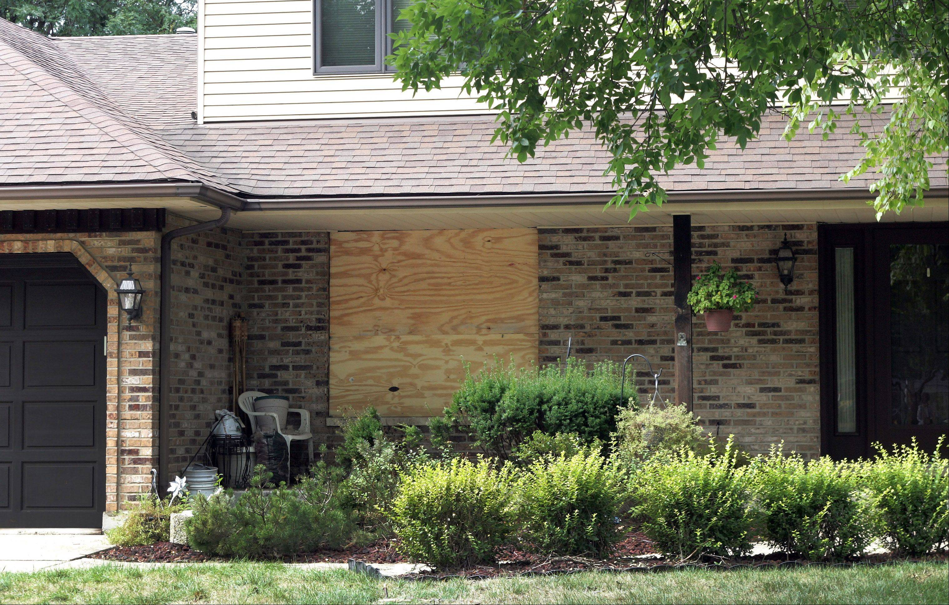 A boarded-up window marks where a car crashed into this house on Robin Hill Drive in Naperville. The teen driver has been charged with two counts of DUI.