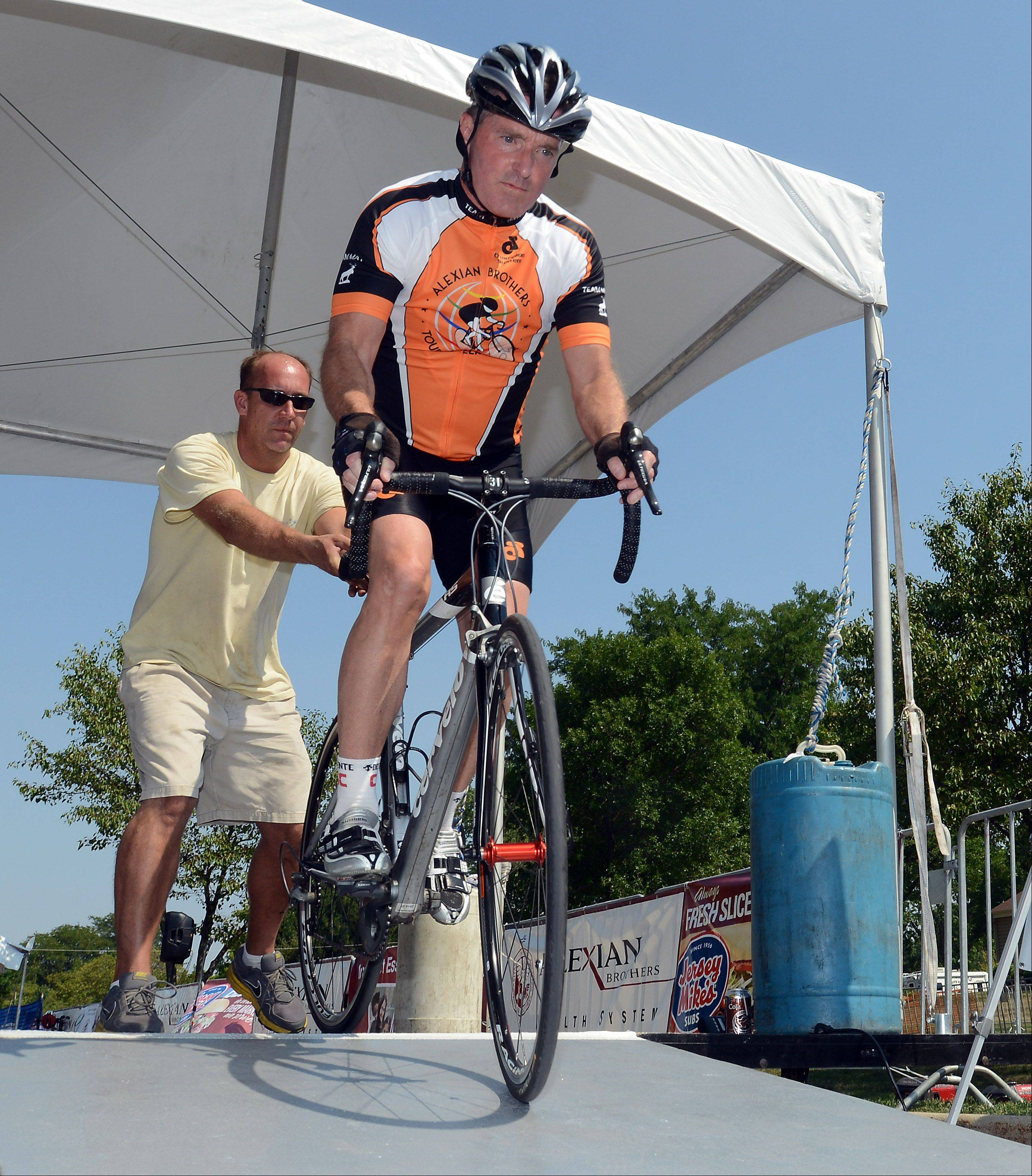 Elk Grove Village Mayor Craig Johnson starts the Mayor Charity Time Trail Race at the Alexian Brothers Tour of Elk Grove on Friday.