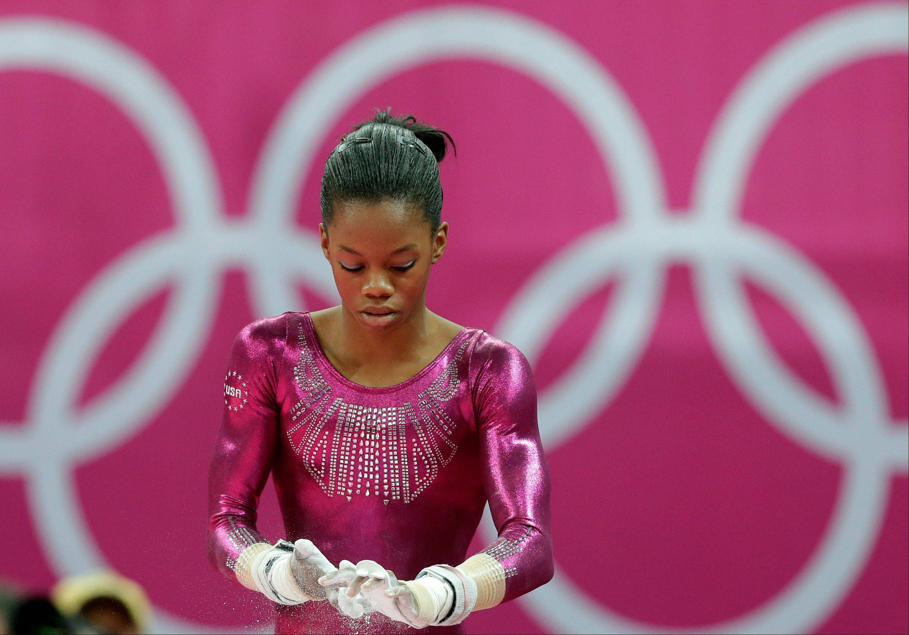 U.S. gymnast Gabrielle Douglas chalks her hands before performing on the uneven bars Thursday during the artistic gymnastics women's individual all-around competition. NBC's researchers are finding that people who know the results of London Olympics events before they are shown on tape delay are more -- not less -- likely to watch them.