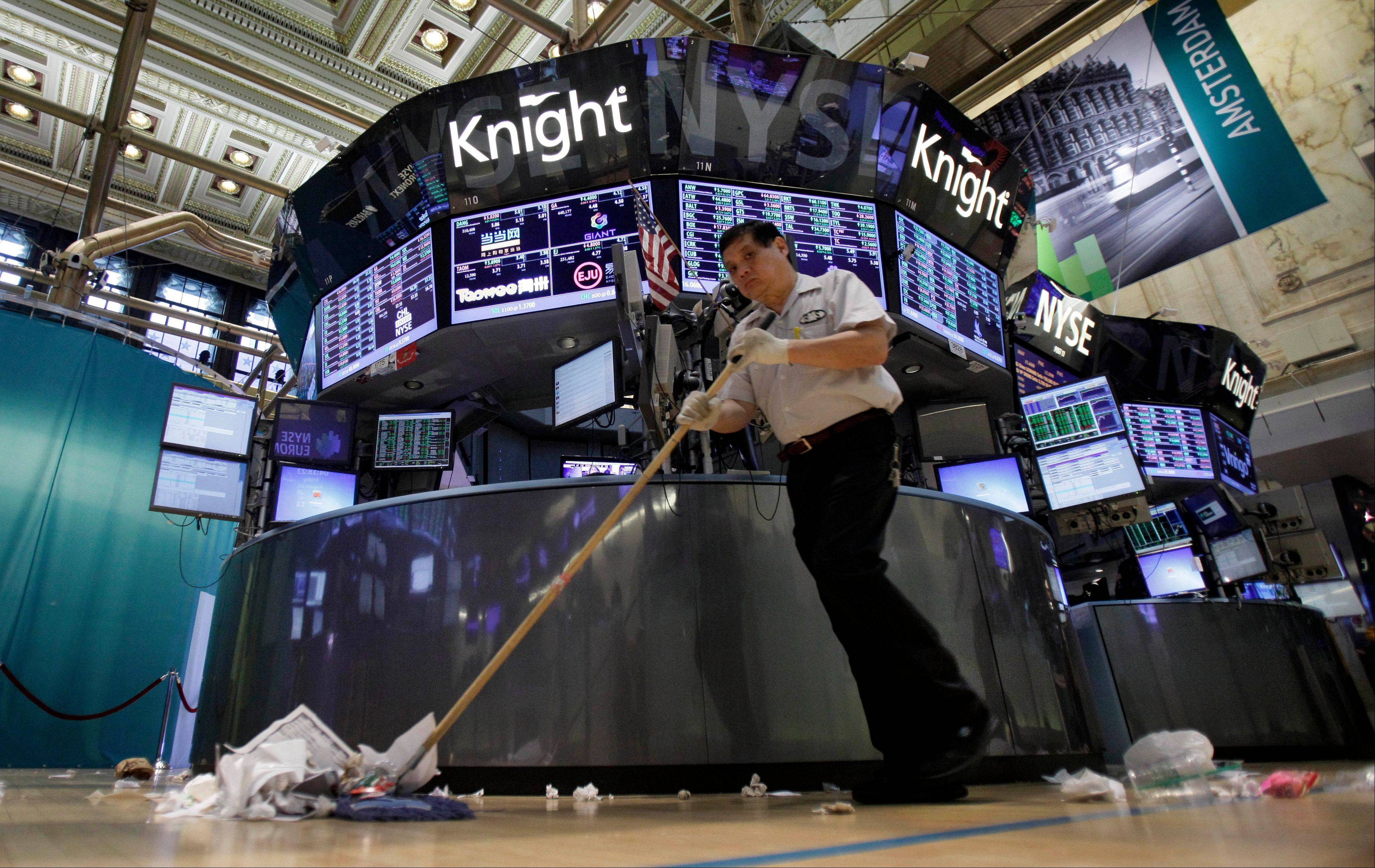 Billy Ying sweeps the floor around the Knight Capital trading post on the floor of the New York Stock Exchange after the close of trading Friday, Aug. 3, 2012. Knight Capital's stock soared after the battered trading firm received a financial lifeline and clients said they expect to resume routing trades through the system. (AP Photo/Richard Drew)