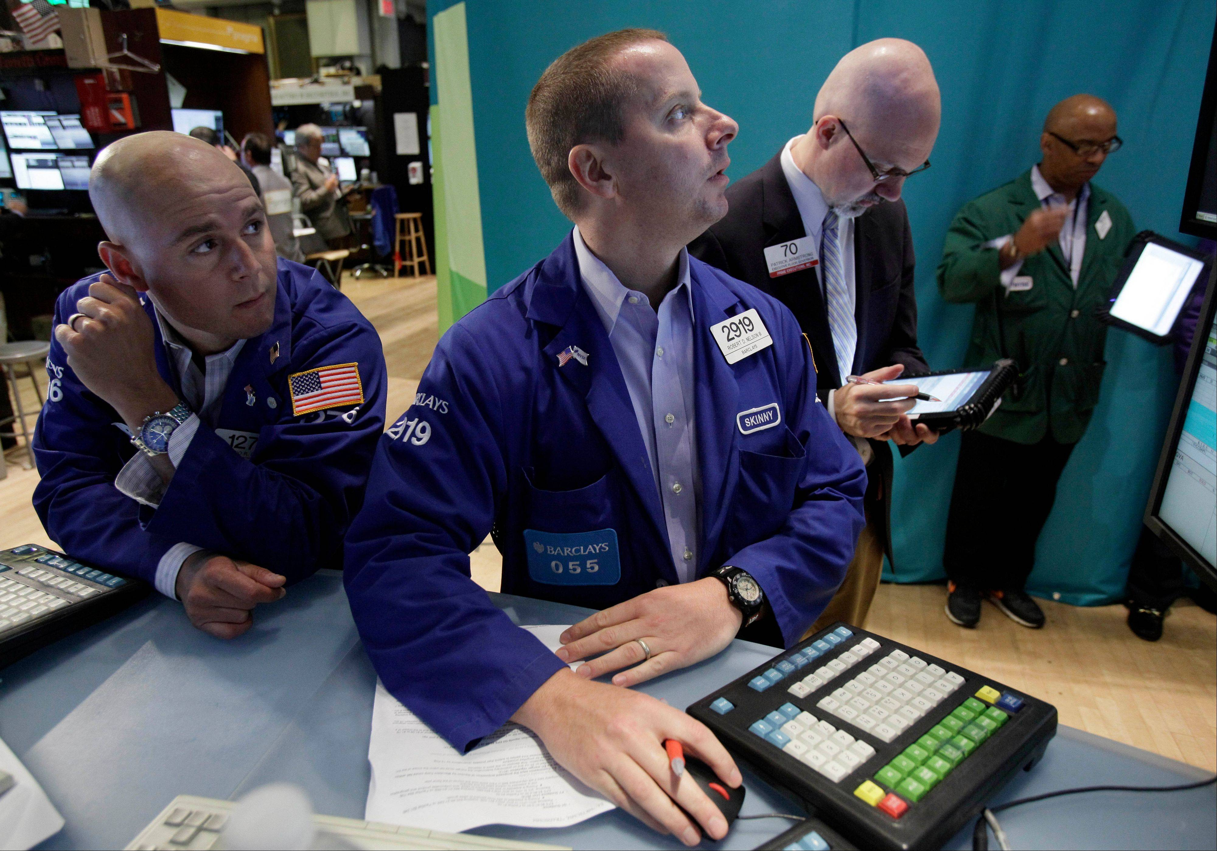 Specialists Mario Picone, left, and Robert Nelson, center, work Friday at their posts on the floor of the New York Stock Exchange. U.S. stocks are rising sharply on Wall Street after a July jobs report revealed the strongest hiring trends in five months.