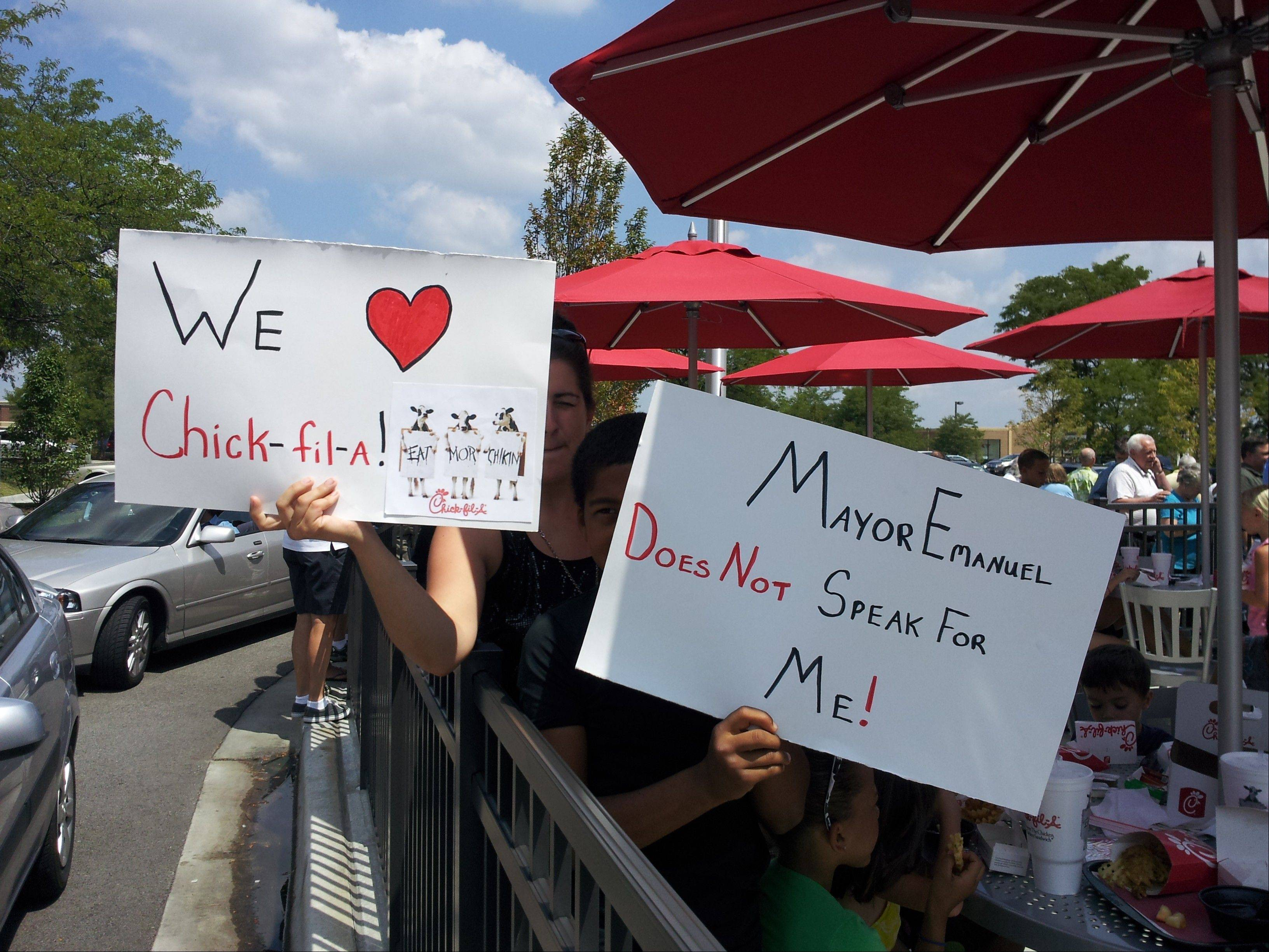 People wave signs Wednesday at the Schaumburg Chick-fil-A to show their support of the restaurant chain president's opposition to same-sex marriage.
