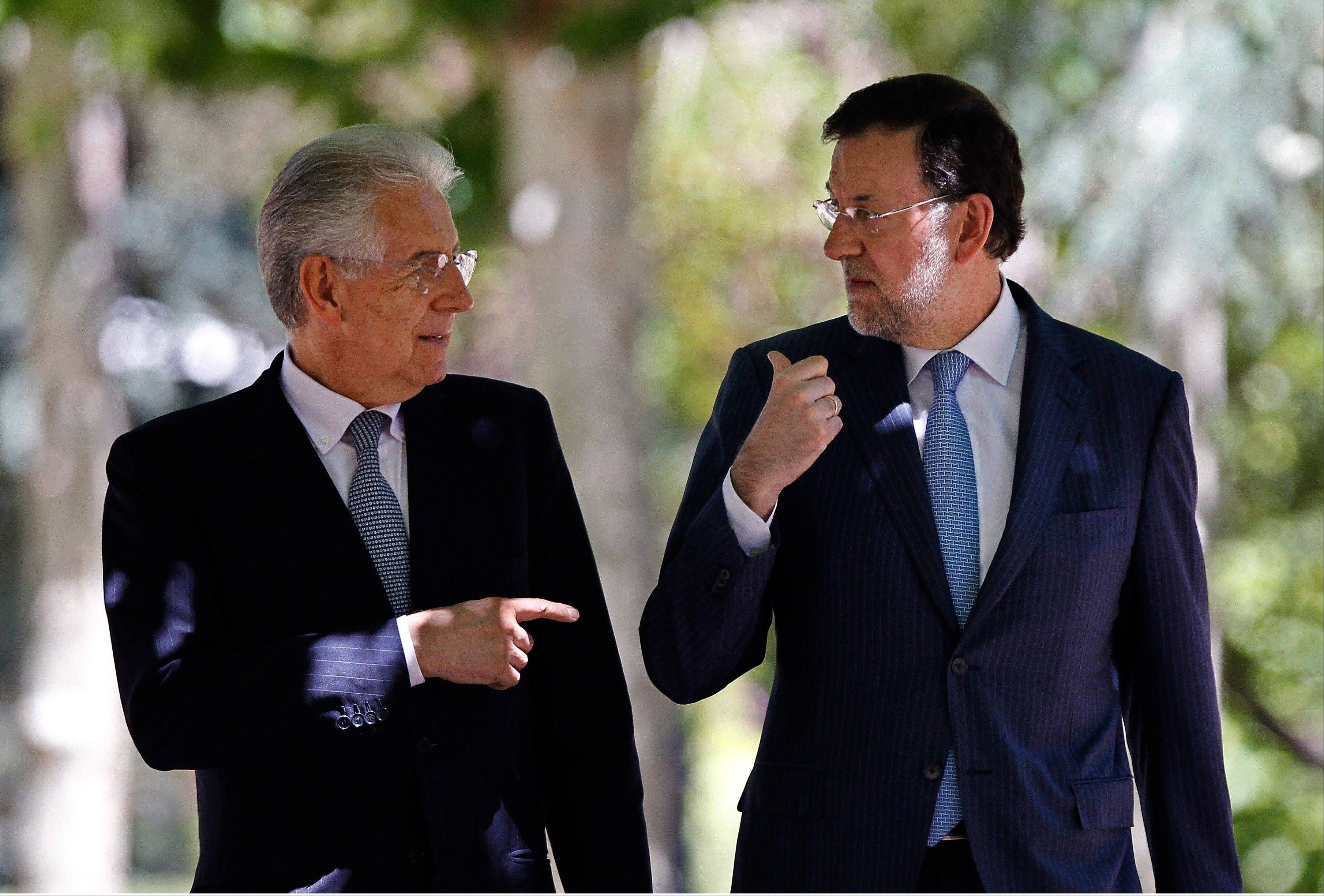 Spain's Prime Minister Mariano Rajoy, right, and Italy's Prime Minister Mario Monti, walk together during a meeting at the Moncloa Palace in Madrid, Spain, Thursday.