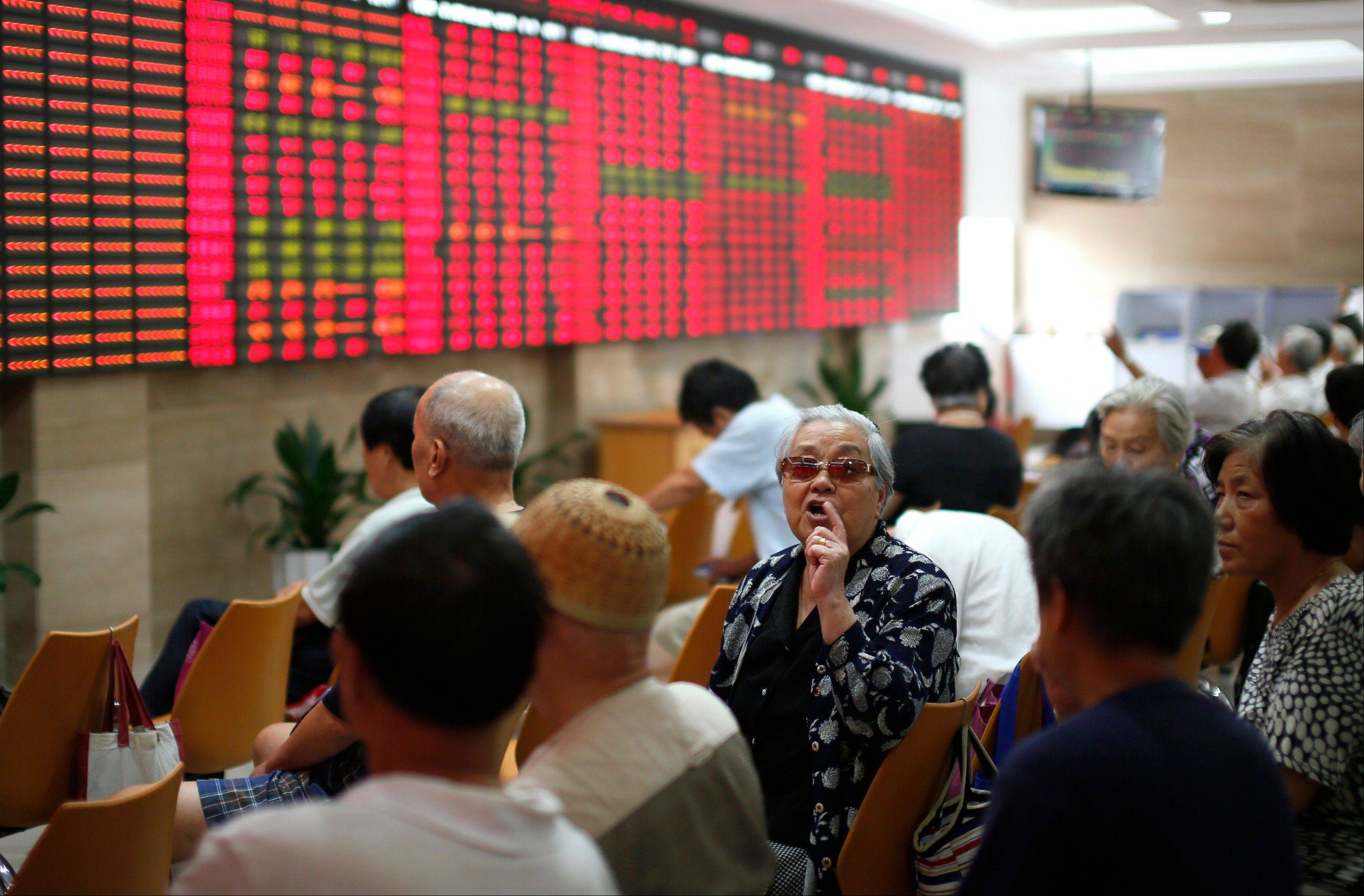 An investor, center, speaks to another while they look at the stock price monitor at a private securities company Friday in Shanghai, China.