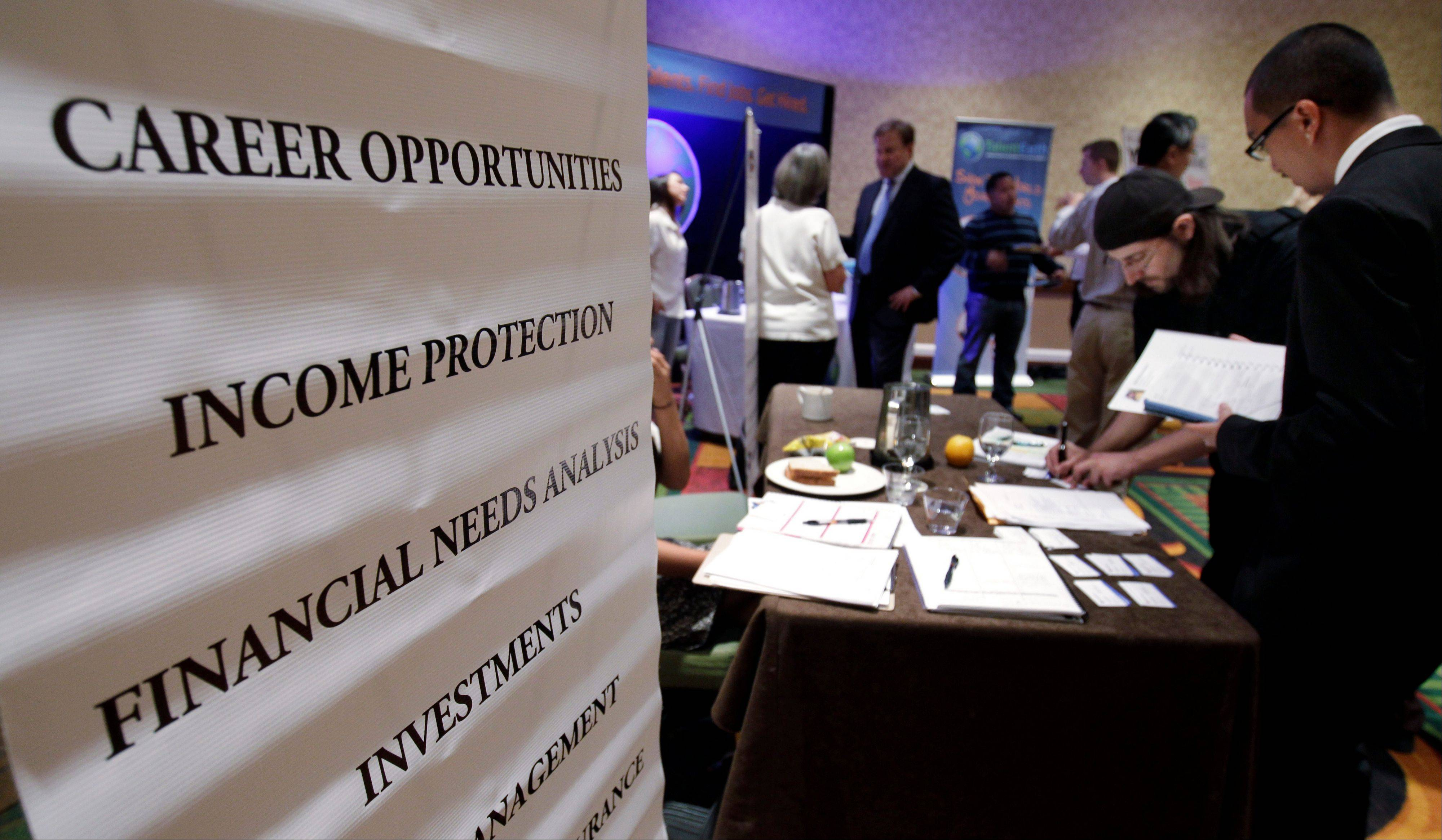 People looking for work talk at a Primerica job booth at a job fair in San Jose, Calif. U.S. hiring was likely sluggish in July for a fourth straight month, held back by slower economic growth and an uncertain outlook.