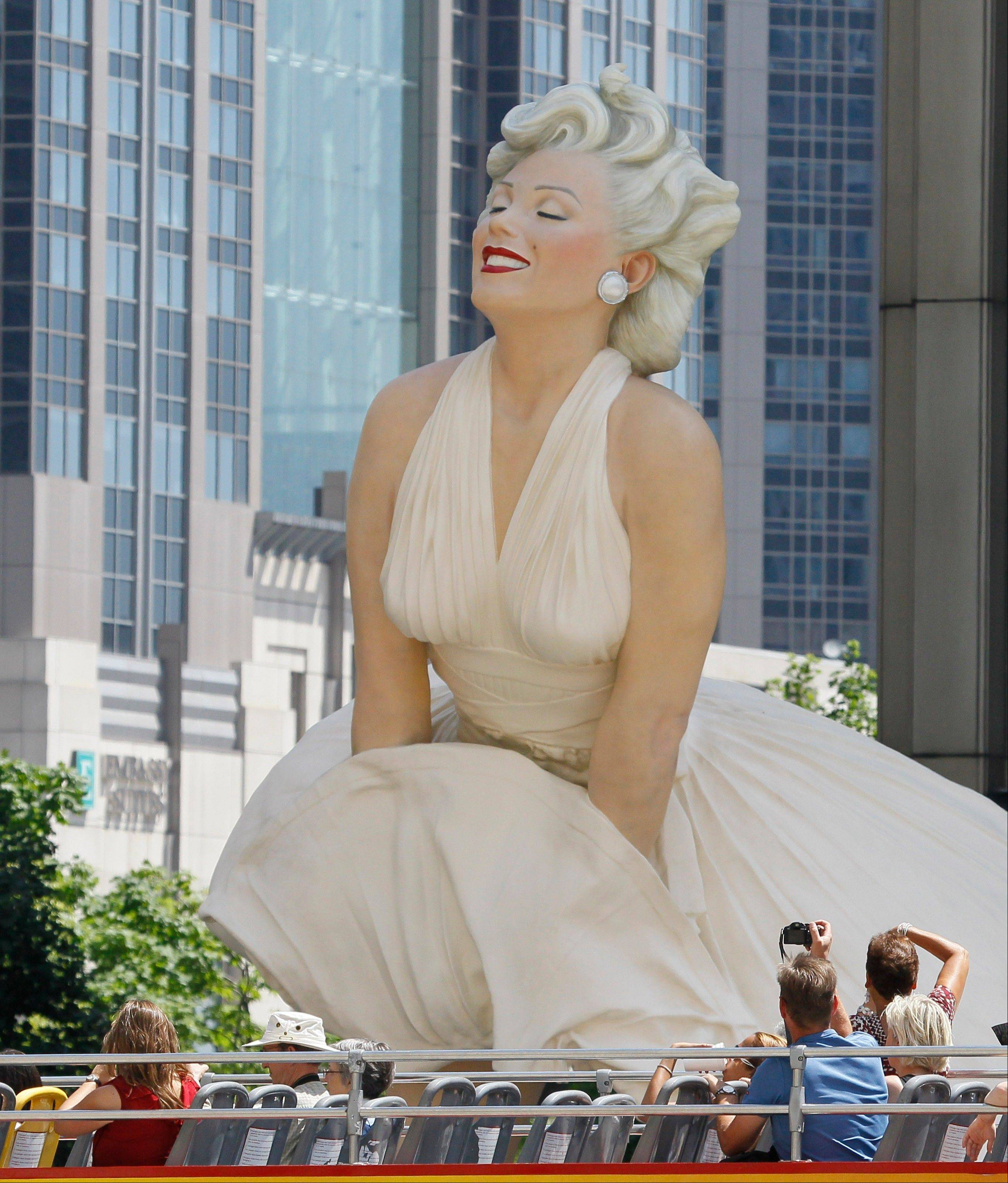 Tourists on a double-decker bus photograph Seward Johnson's 26-foot-tall sculpture of Marilyn Monroe, in her most famous windblown pose, when it was in Chicago last year.