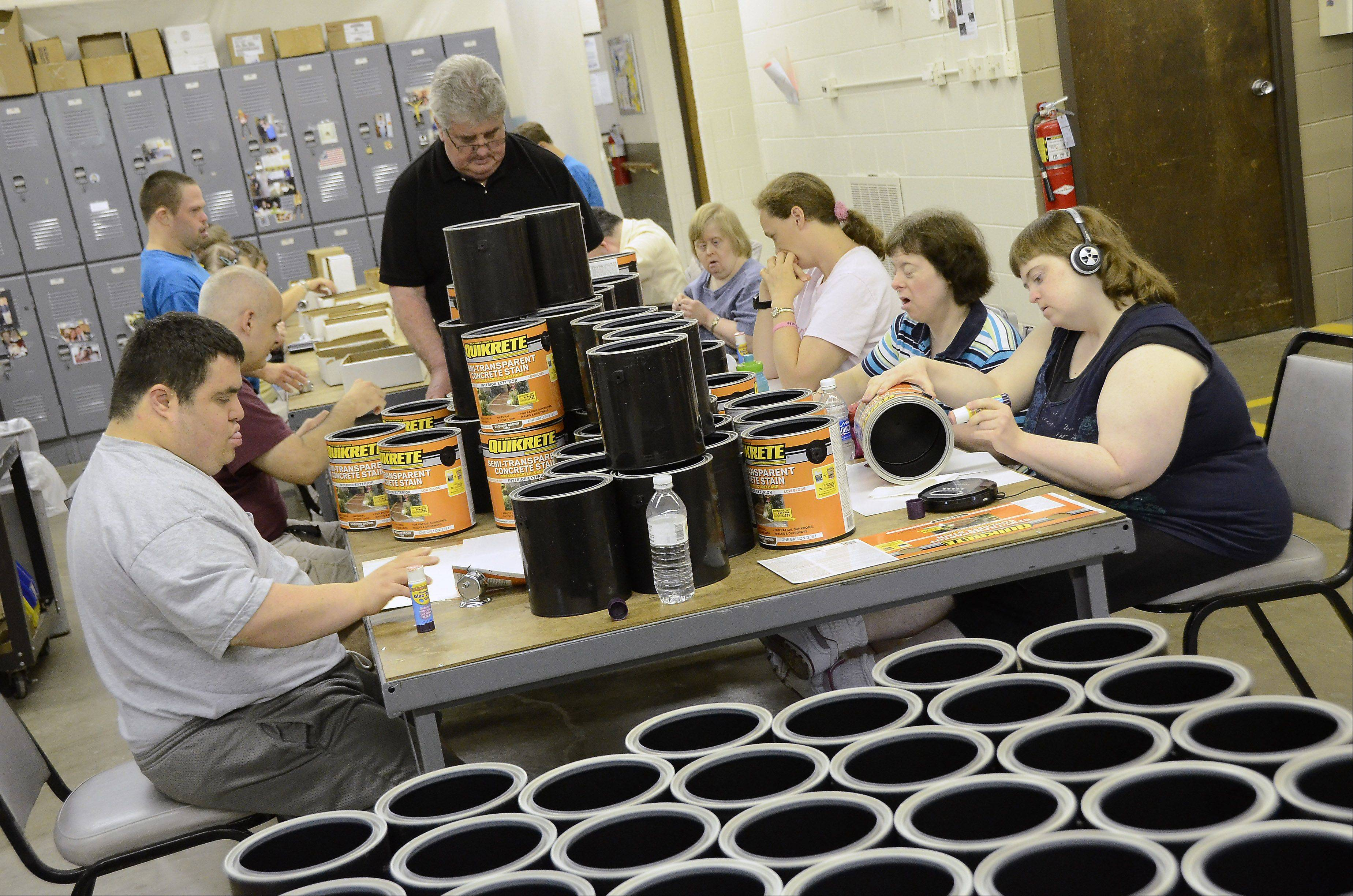 Clients at Countryside Association for People with Disabilities affix labels to paint cans for Sunnyside Corp. The organization next week will open its new 9,000-square-foot addition.