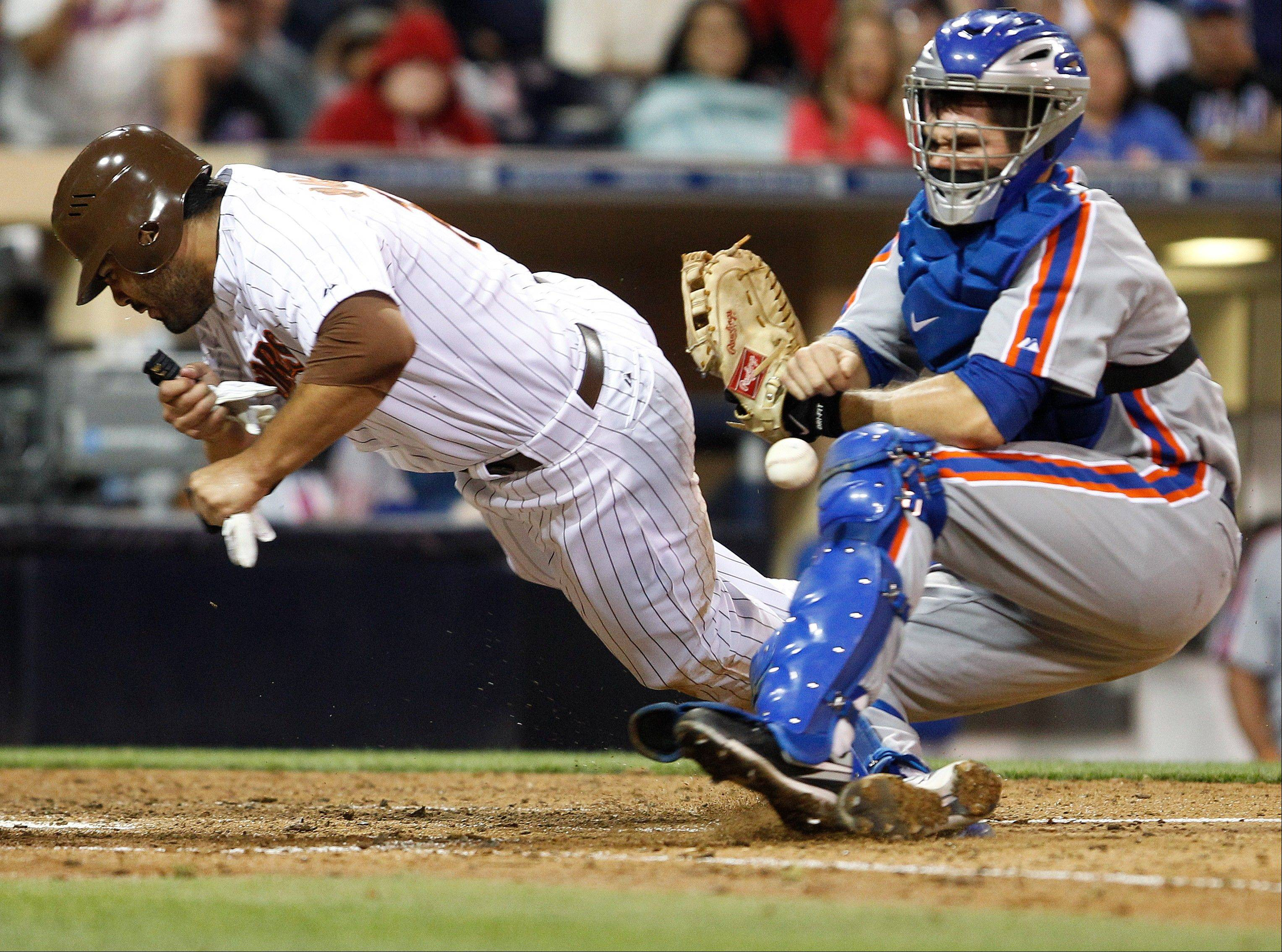 The Padres' Carlos Quentin knocks the ball loose as he plows into New York Mets catcher Josh Thole during the seventh inning Friday in San Diego.