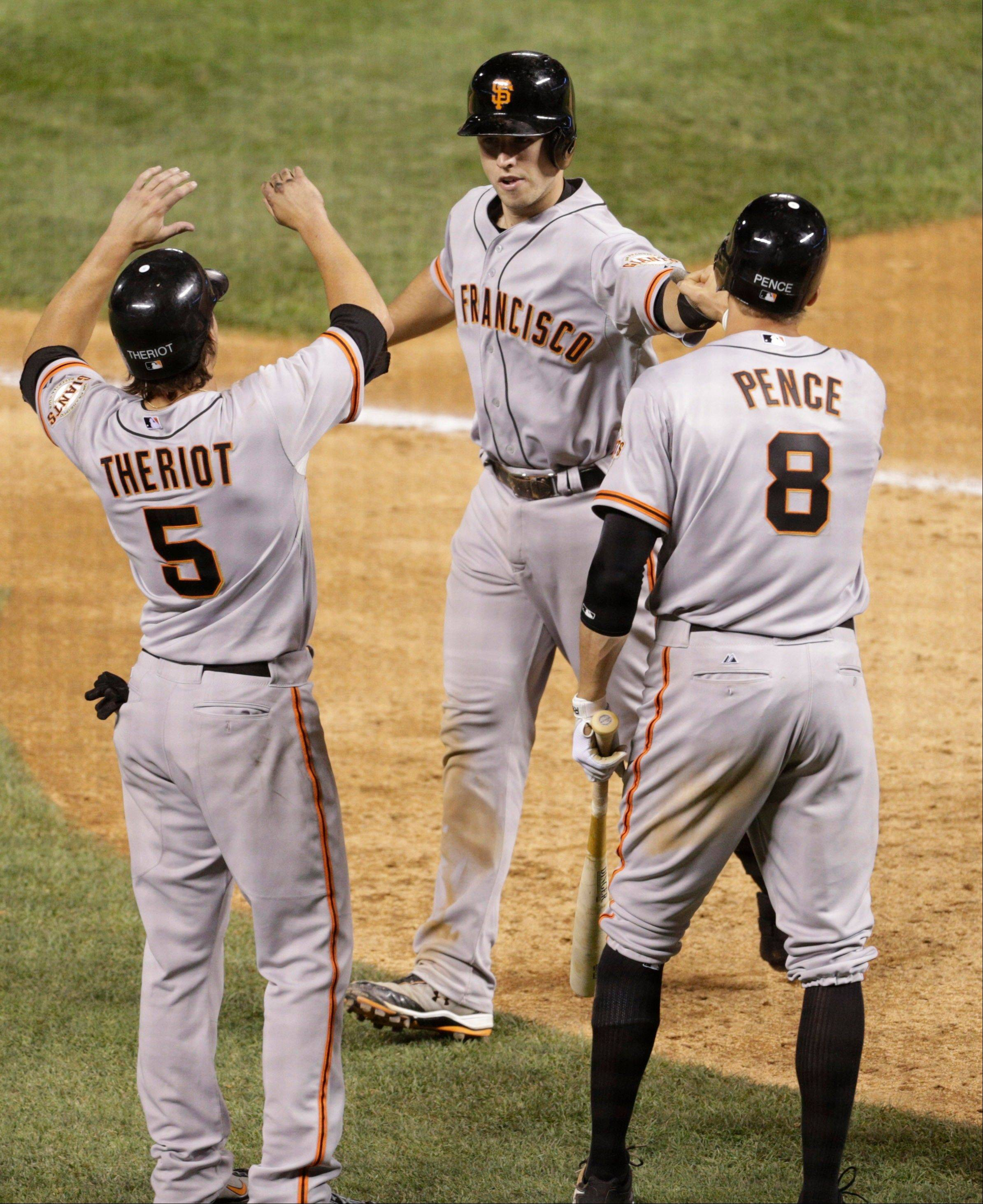 The Giants' Ryan Theriot (5) and Hunter Pence (8) congratulate teammate Buster Posey after his three-run home run in the eighth inning Friday in Denver.