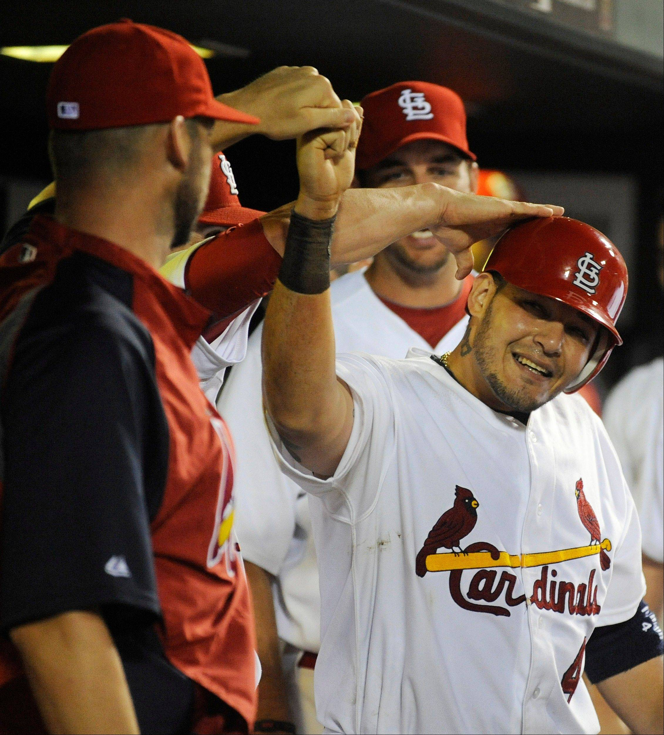 The Cardinals' Yadier Molina is congratulated by teammates after scoring against the Milwaukee Brewers in the sixth inning Friday in St. Louis.