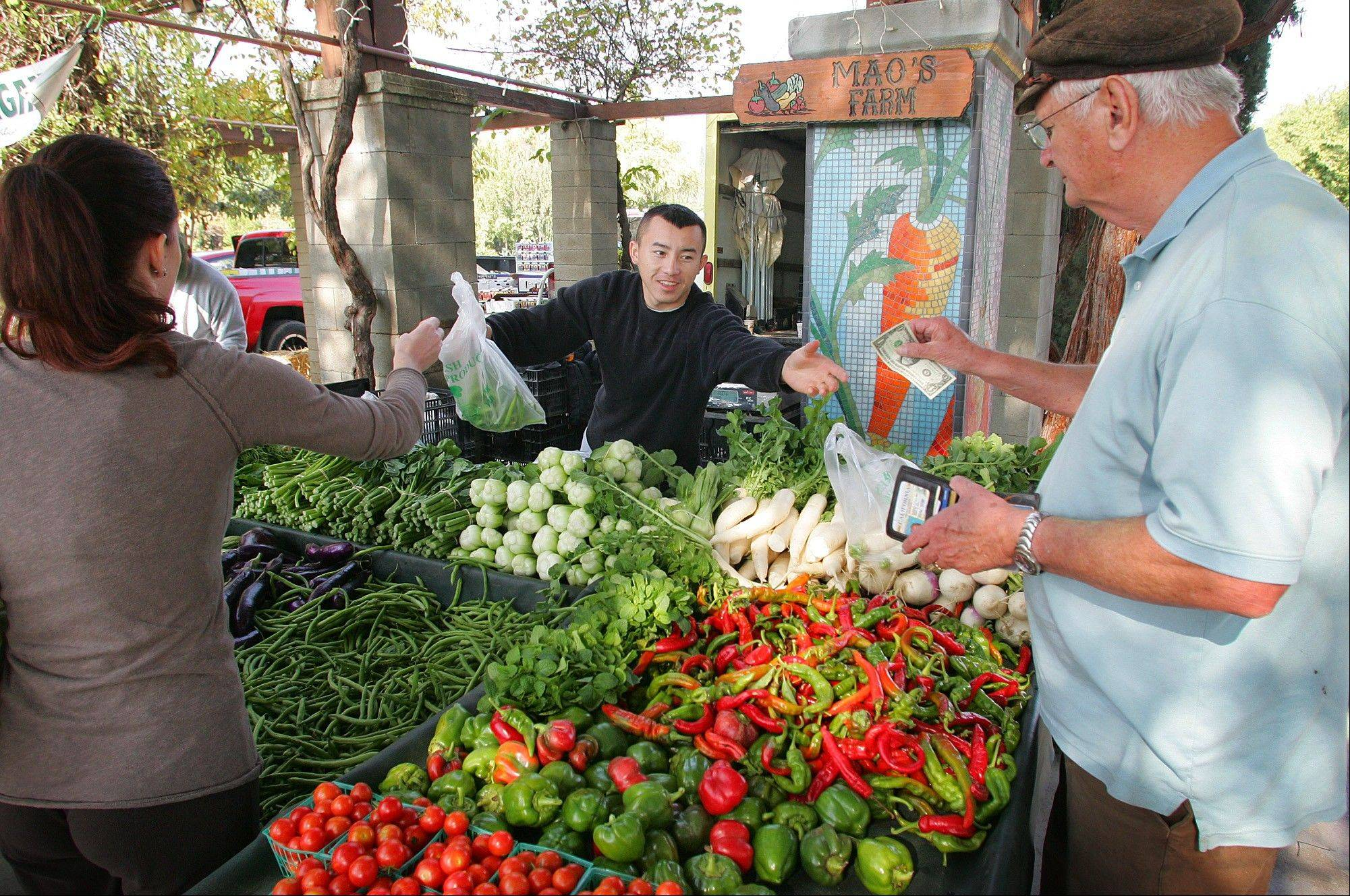 Ching Thao, of Mao's Farm, center, gives change to Richard Wolk, right, at the Vineyard Farmers Market in Fresno, Calif.