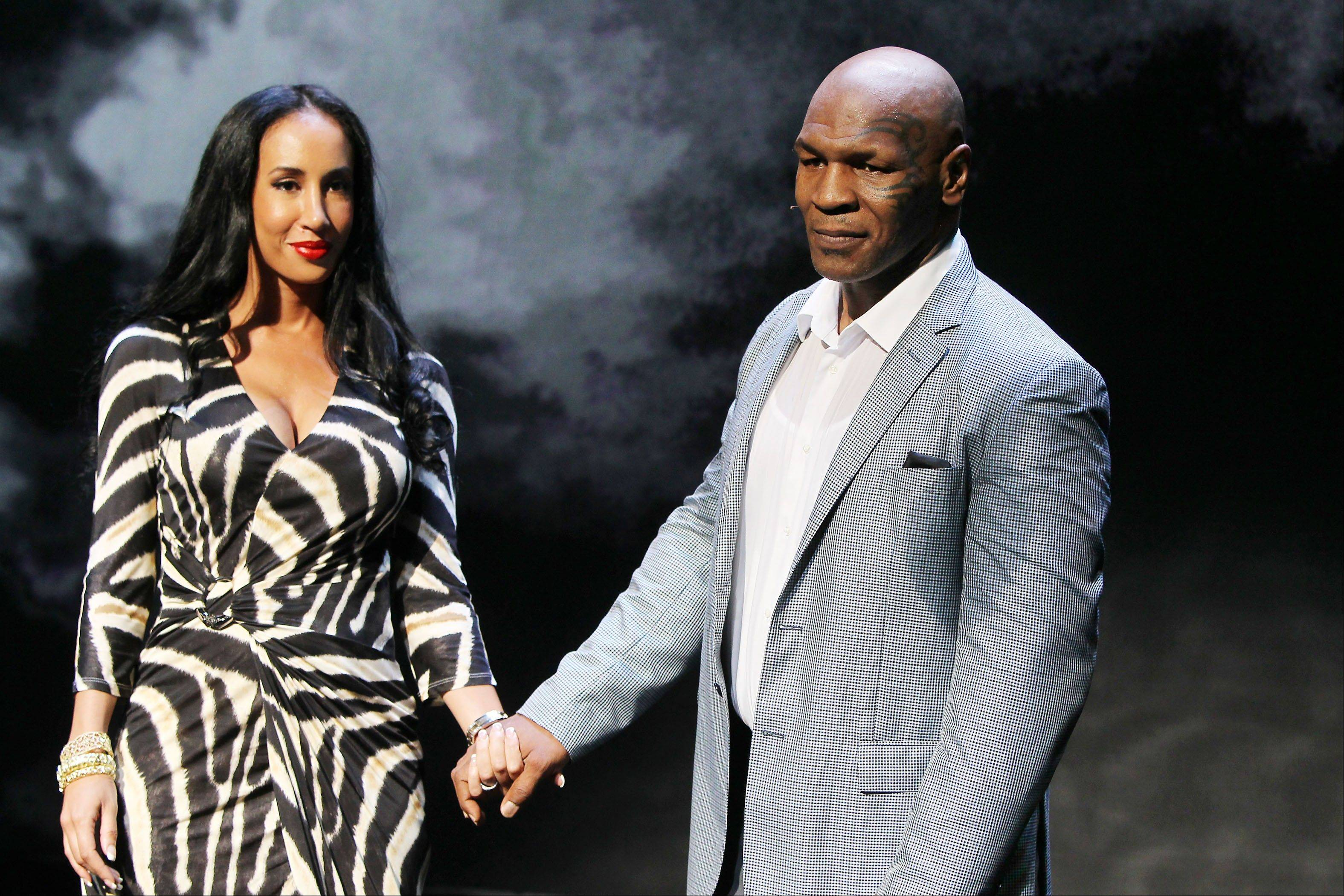 "Former boxer Mike Tyson holds hands with his wife, Kiki, at the curtain call for the opening night of ""Mike Tyson: Undisputed Truth"" on Thursday in New York. The one-man show starring Tyson was directed by Spike Lee and written by Kiki."