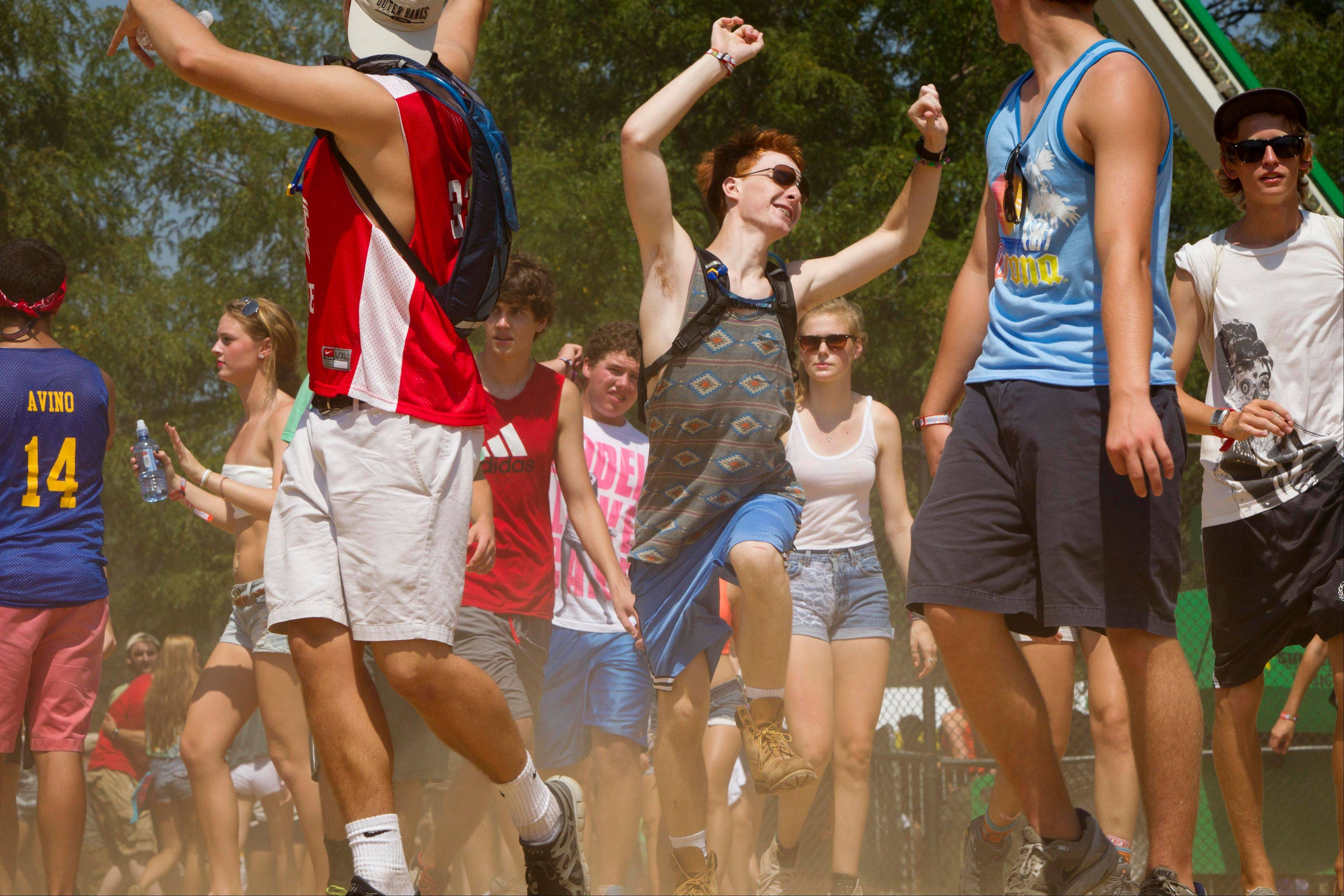 Fans dance their way between stages at Lollapalooza in Chicago's Grant Park on Friday, Aug. 3, 2012.